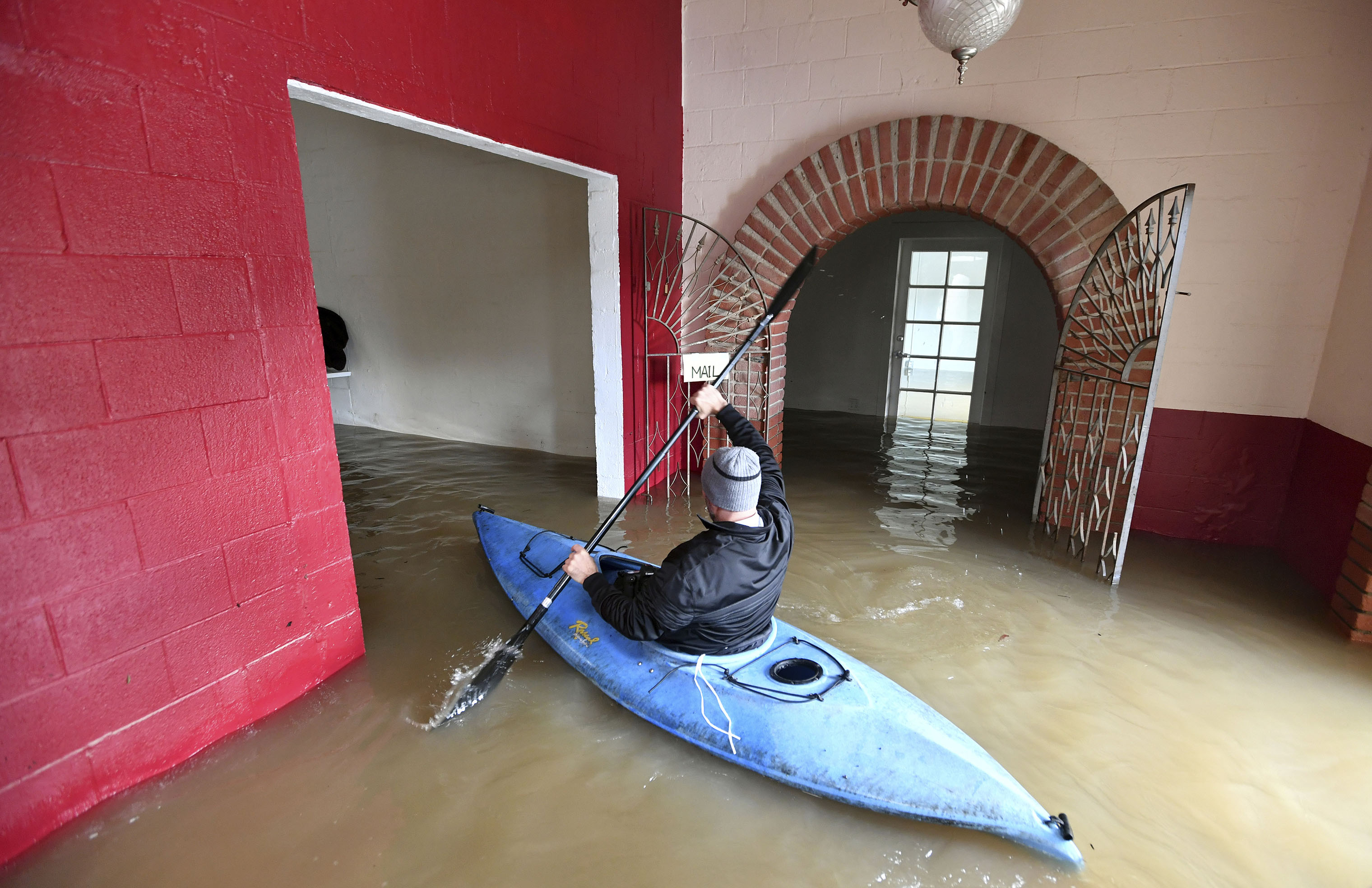 Jay Michael Tucker kayaks through the flooded Surrey Resort as the Russian River flows through it in Guerneville, Calif., on Feb. 15, 2019.