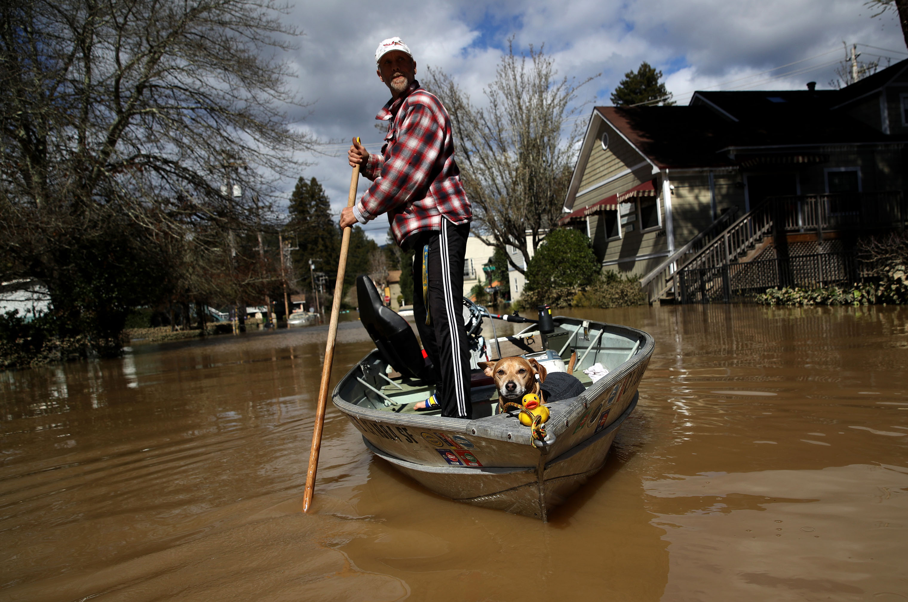 A resident and his dog navigate through a flooded neighborhood on Feb. 28, 2019 in Guerneville, California.