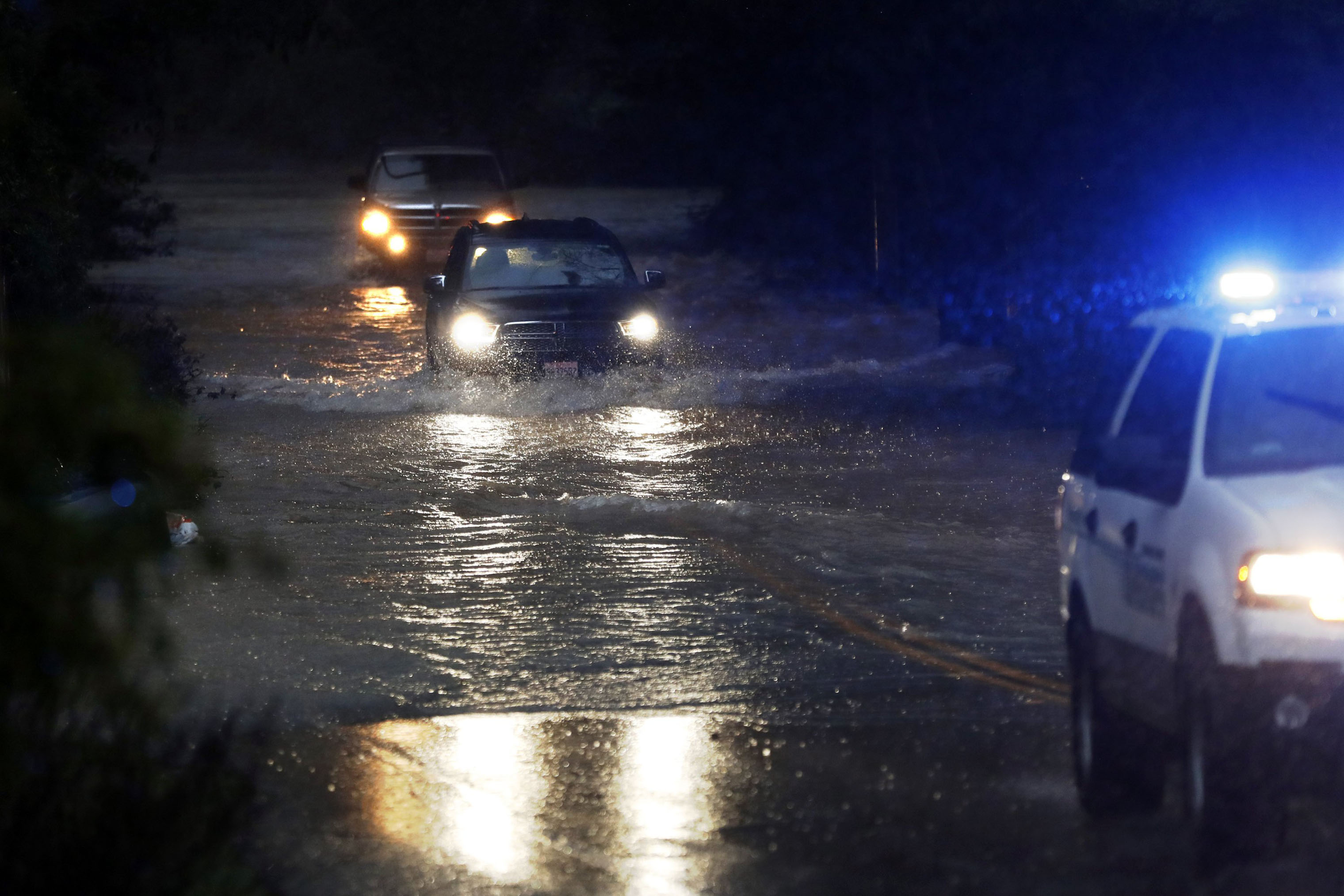 Two vehicles follow a Sonoma County Sheriff's vehicle through flooded Neeley Road as the Russian River rises towards flood stage in Guerneville, California on Feb. 26, 2019. The Sonoma County Sheriff's Office issued mandatory evacuations in communities along the Russian River and urged people to  evacuate now.  As of 9:32 p.m. on Feb. 26, the river had reached 35.1 feet.