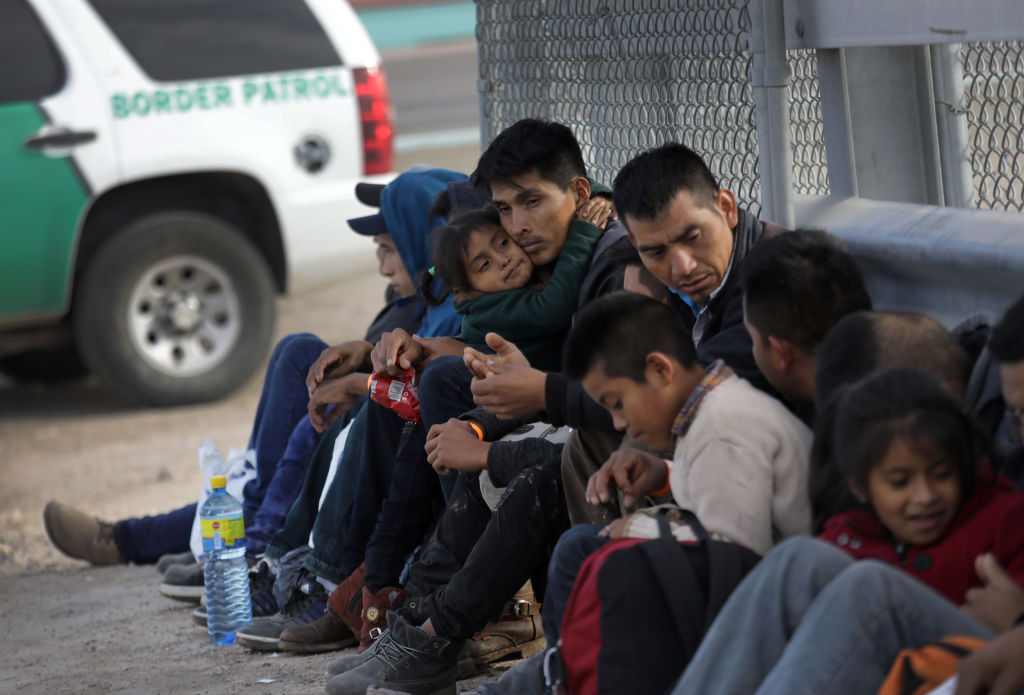 Central American migrants wait to be taken into custody and turning themselves in for political asylum after crossing into the United States from Mexico on Feb. 1, 2019 in El Paso, Texas.