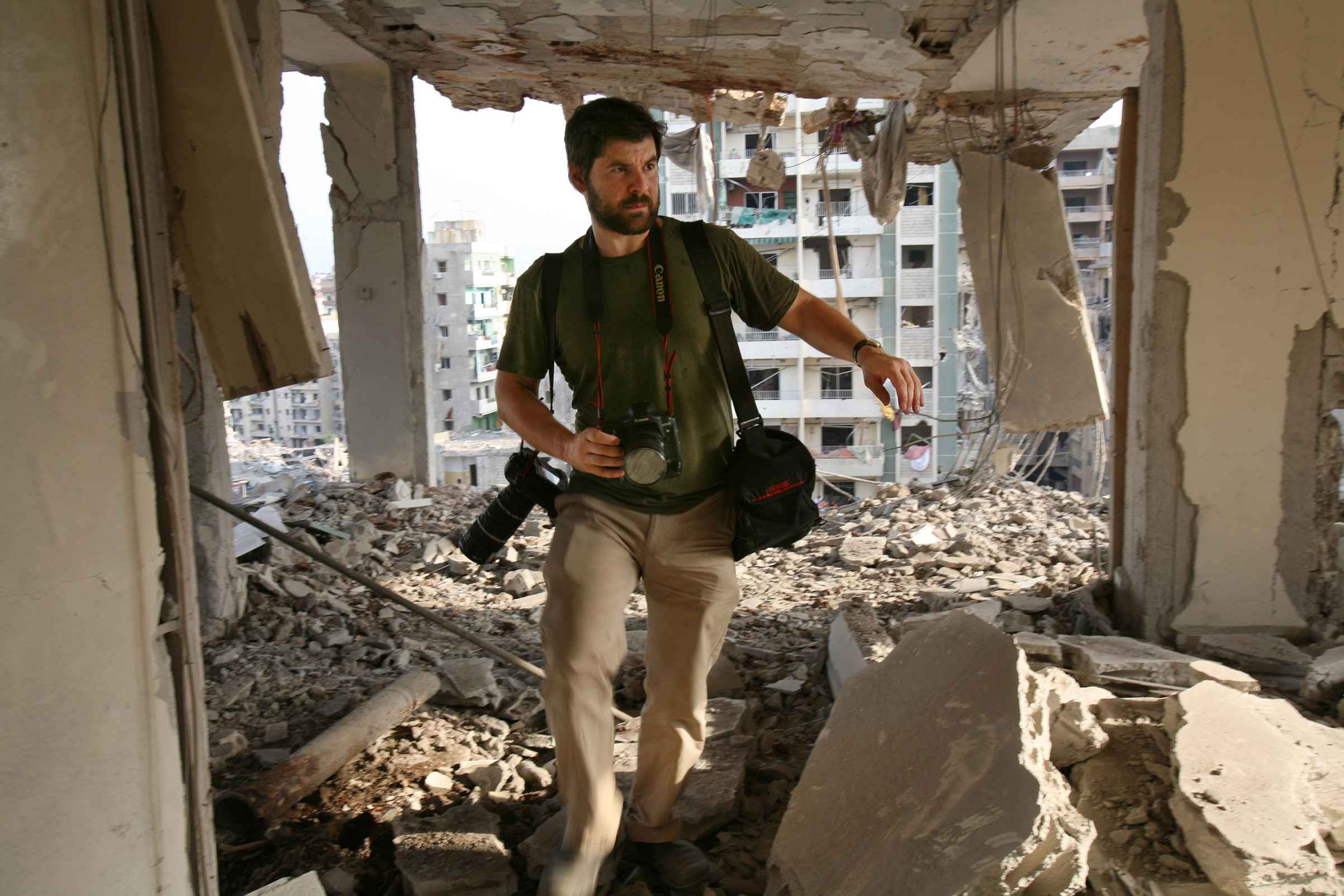 Getty Images photographer Chris Hondros walks through the ruins of a building in southern Beirut on Aug. 21, 2006. Hondros was killed while on assignment in Misrata, Libya, on April 20, 2011.