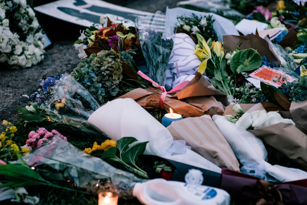 Flowers are left as people attend a vigil for the lives taken in the Christchurch terror attacks at the Auckland Domain on March 22, 2019 in Auckland, New Zealand.