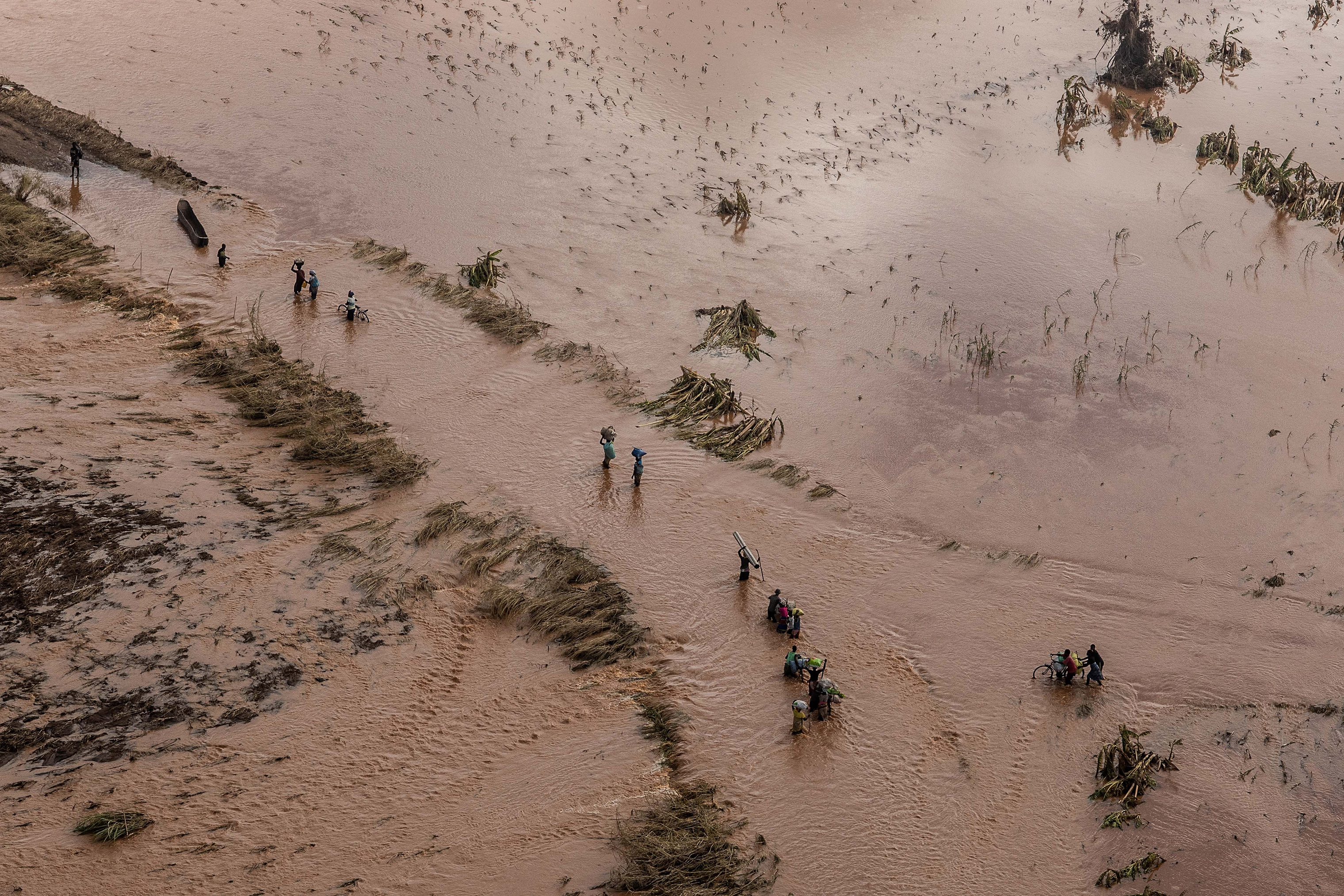 People wade through flood waters in a rural neighborhood affected by Cyclone Idai on March 24, 2019 in Buzi, Mozambique.