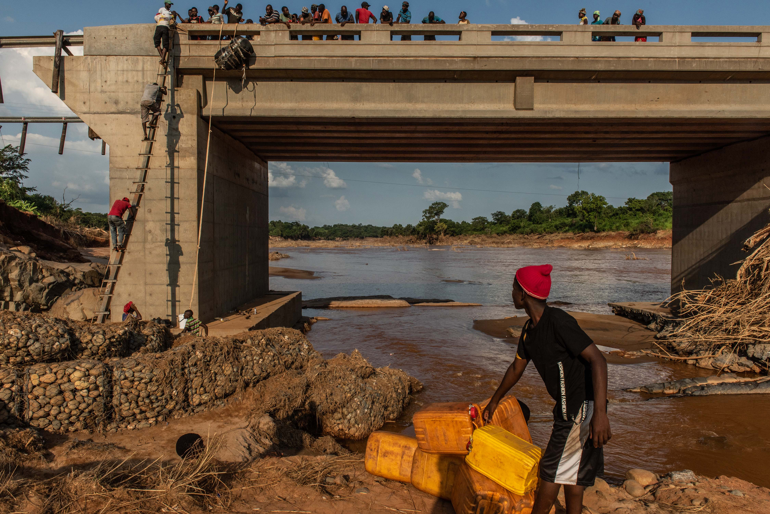 People climb to the top of a broken bridge, damaged during Cyclone Idai, across the Lucite River on March 26, 2019, outside of Magaro, Mozambique.
