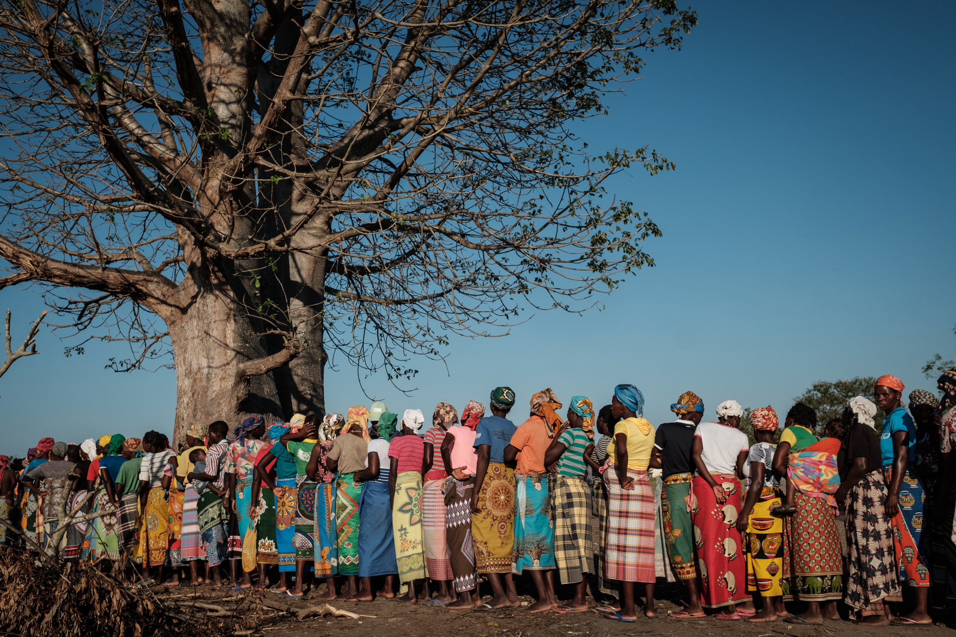 Women wait in a line to receive relief supplies from a South African relief organization in Estaquinha, Mozambique, on March 26, 2019.