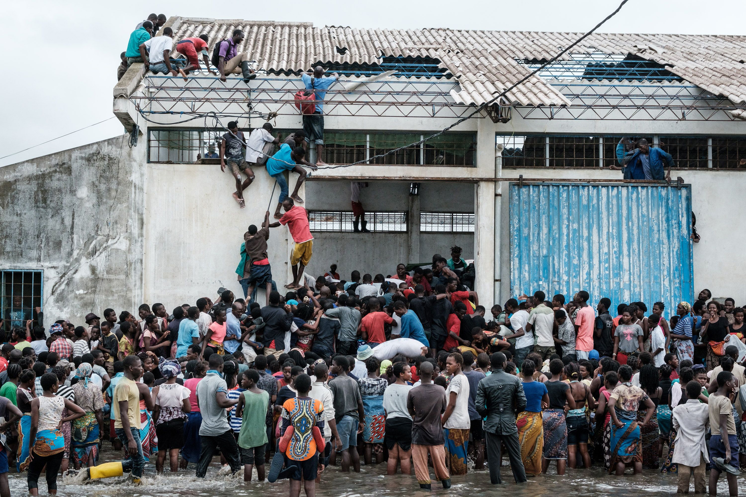 People looting sacks of Chinese rice from a warehouse surrounded by water in Beira, Mozambique, on March 20, 2019.
