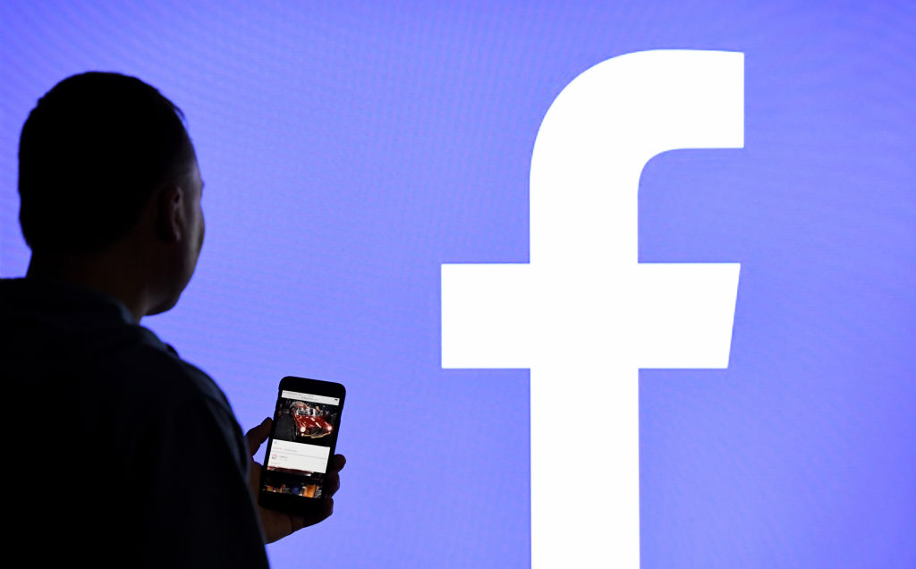 A man with a smartphone stands in front of a monitor with the Facebook logo on March 15, 2019.