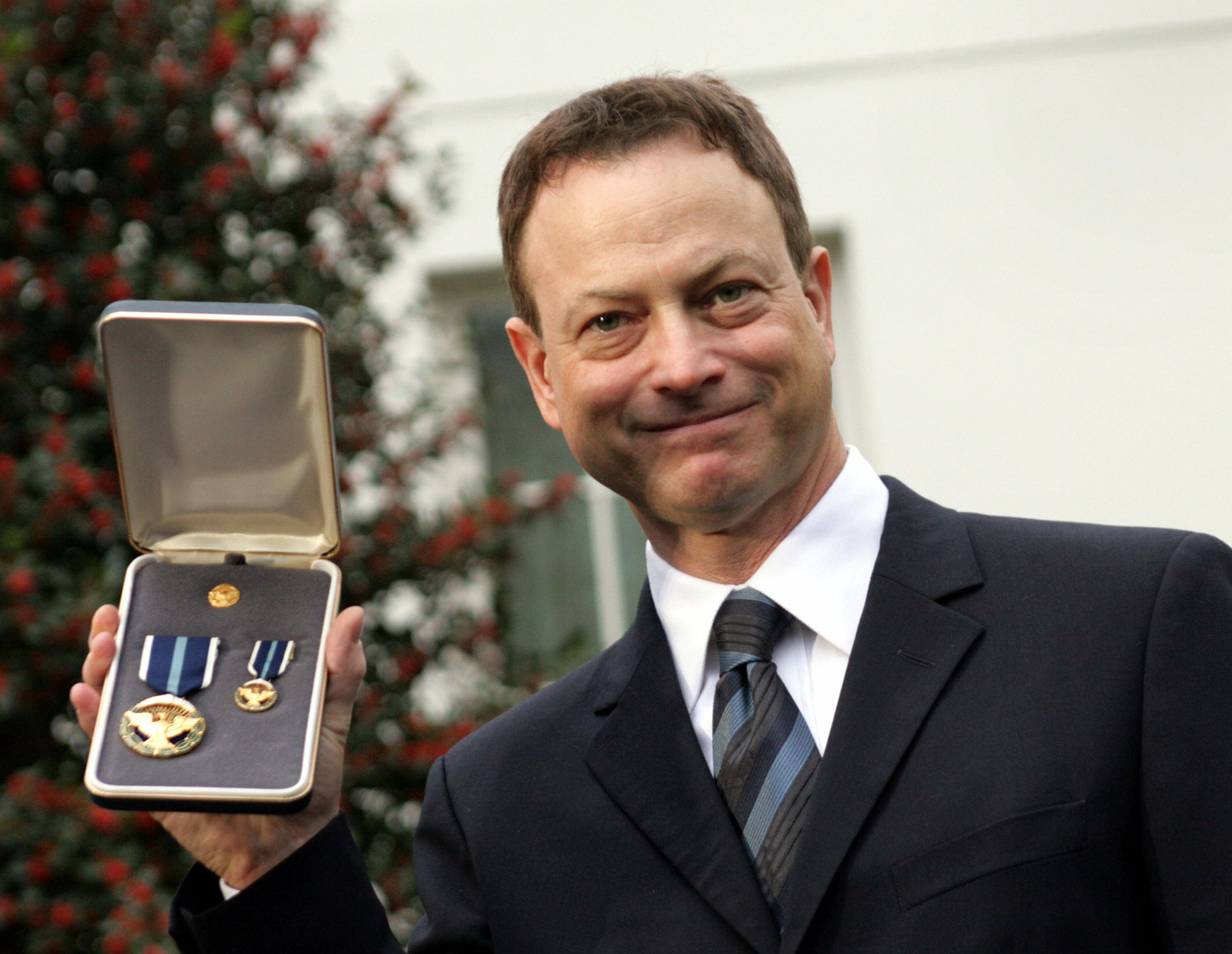 Actor Gary Sinise shows his Presidential Citizens Medal outside the White House in Washington, DC after receiving the medal from US President George W. Bush for his work supporting American soldiers on December 10, 2008.