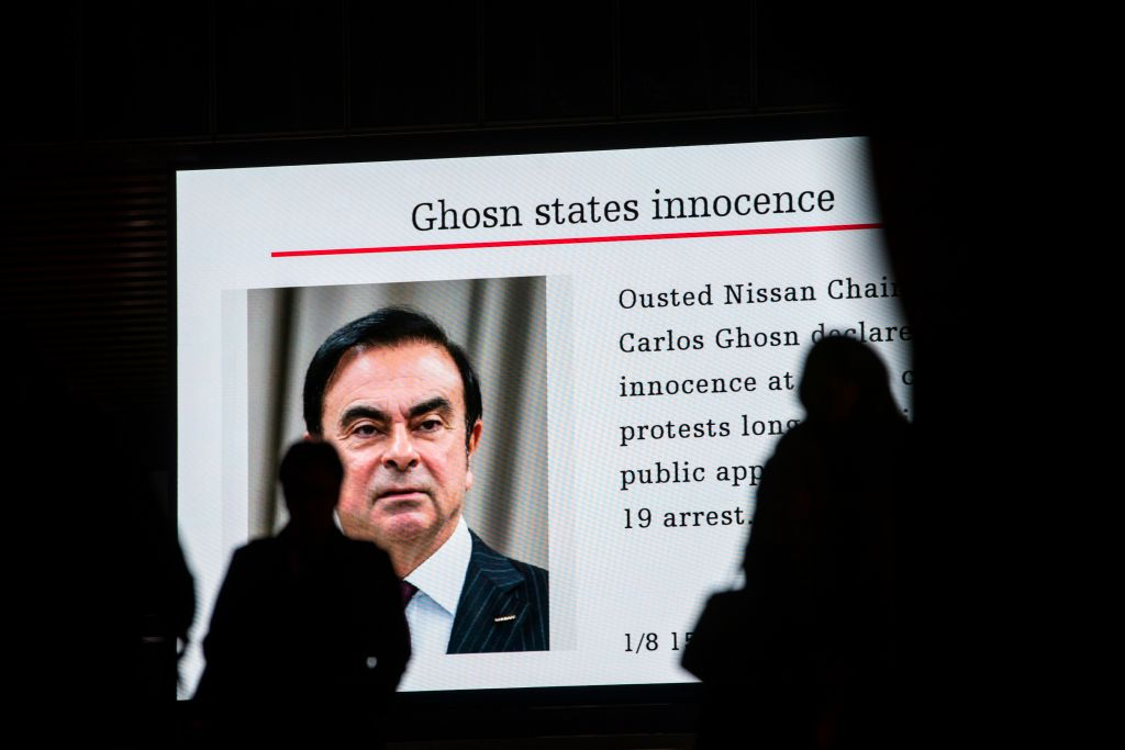 Pedestrians pass by a television screen showing a news program featuring former Nissan chief Carlos Ghosn in Tokyo on Jan. 8, 2019.