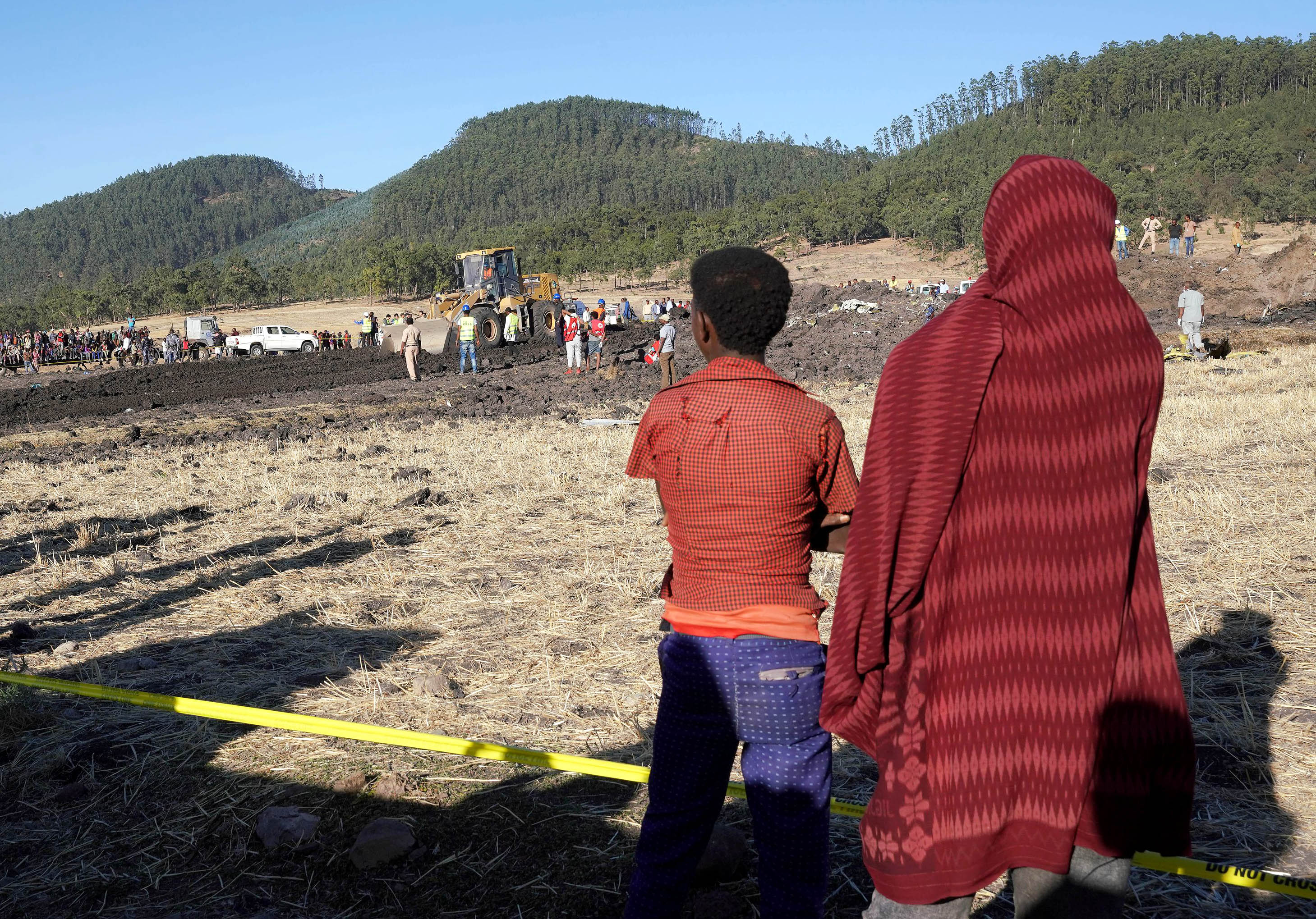 Local residents watch as rescue personnel recover debris from the crater where Ethiopian Airlines Flight 302 crashed southeast of Addis Ababa on March 10, 2019.