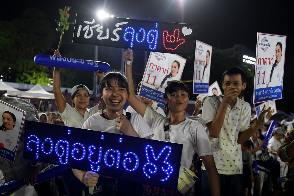 Supporters of the Phalang Pracharat party hold signs during the party's final major campaign rally in Bangkok on March 22, 2019