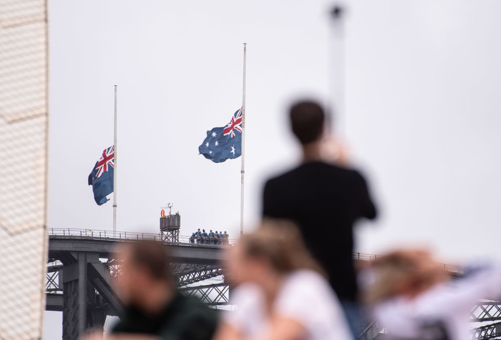 Flags fly at half mast on the Sydney Harbour Bridge in Sydney, Australia on March 16, 2019.
