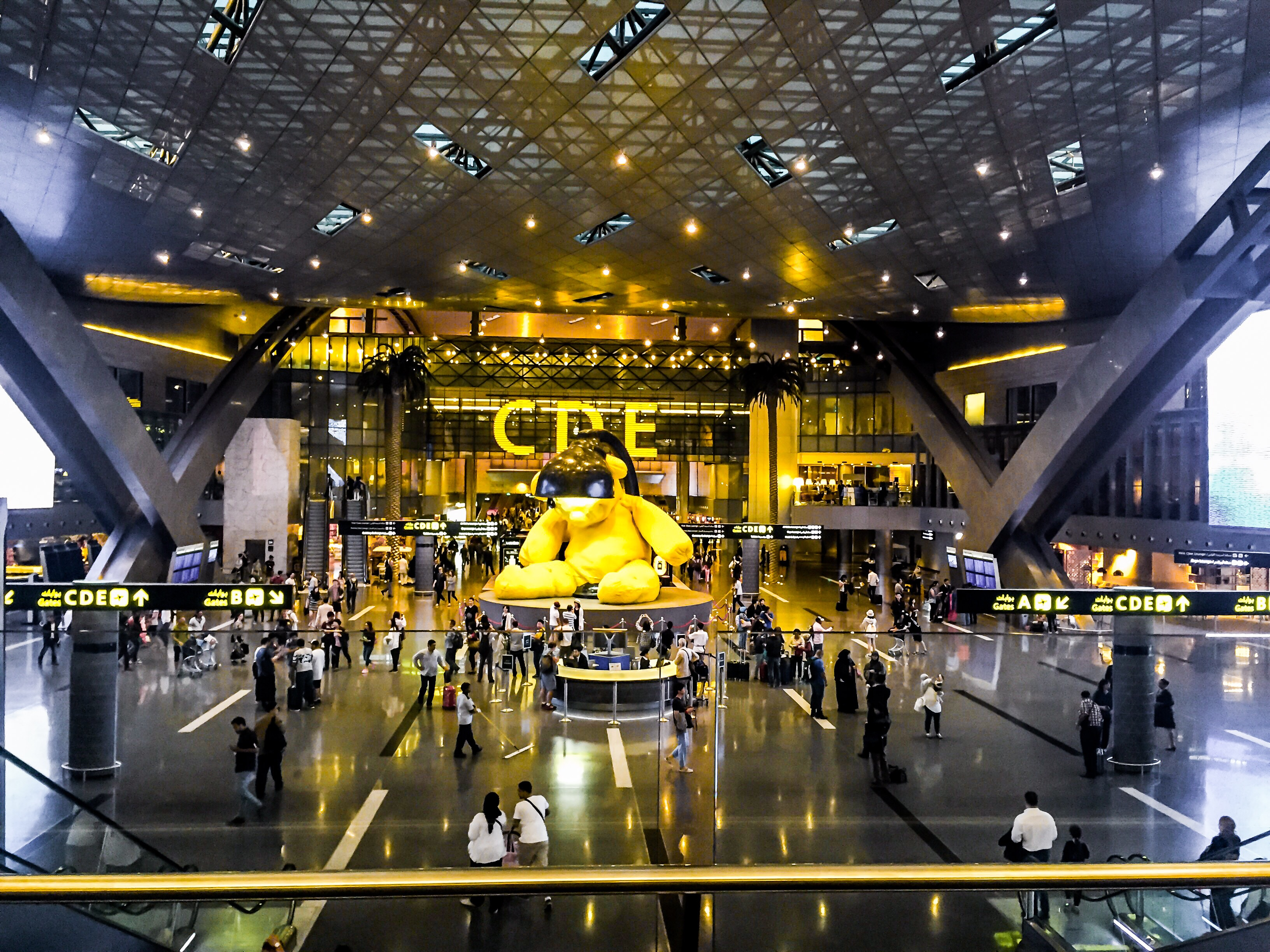 Main area of Hamad International Airport, with a giant yellow teddy bear statue in the center.