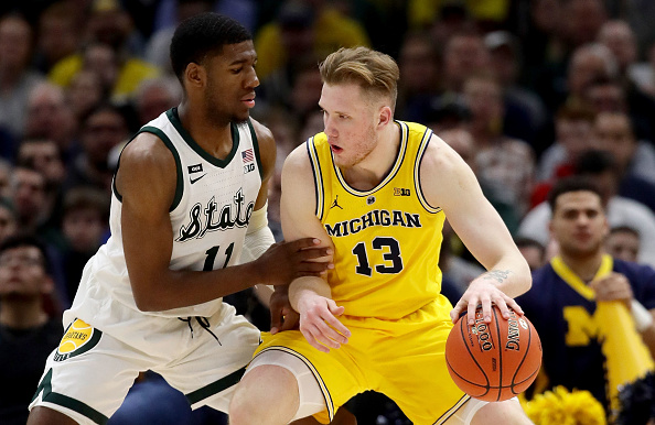 Ignas Brazdeikis #13 of the Michigan Wolverines dribbles the ball while being guarded by Aaron Henry #11 of the Michigan State Spartans in the second half during the championship game of the Big Ten Basketball Tournament at the United Center in Chicago, Illinois on March 17, 2019.