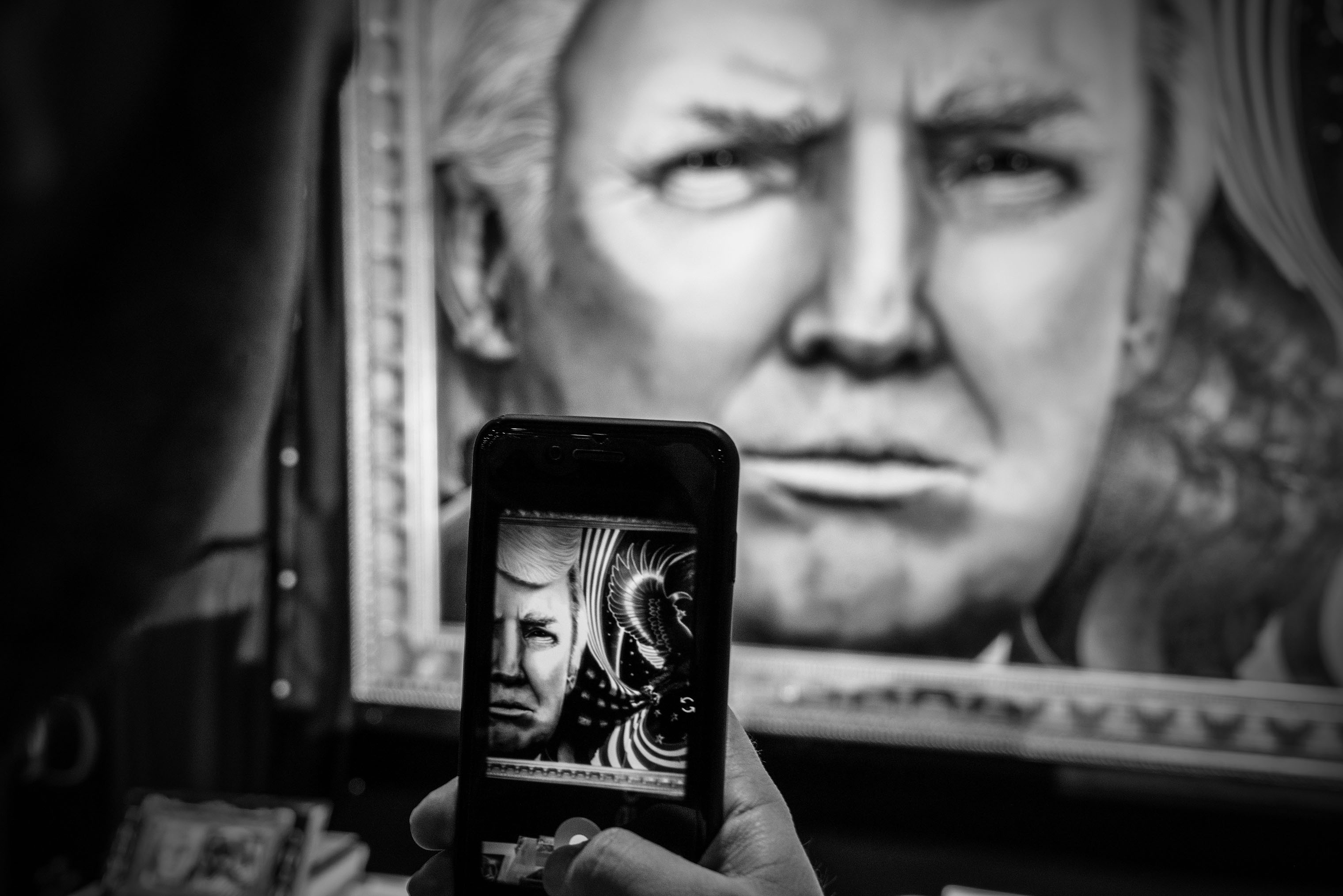 An attendee takes a photo of a painting of President Donald Trump with their phone.