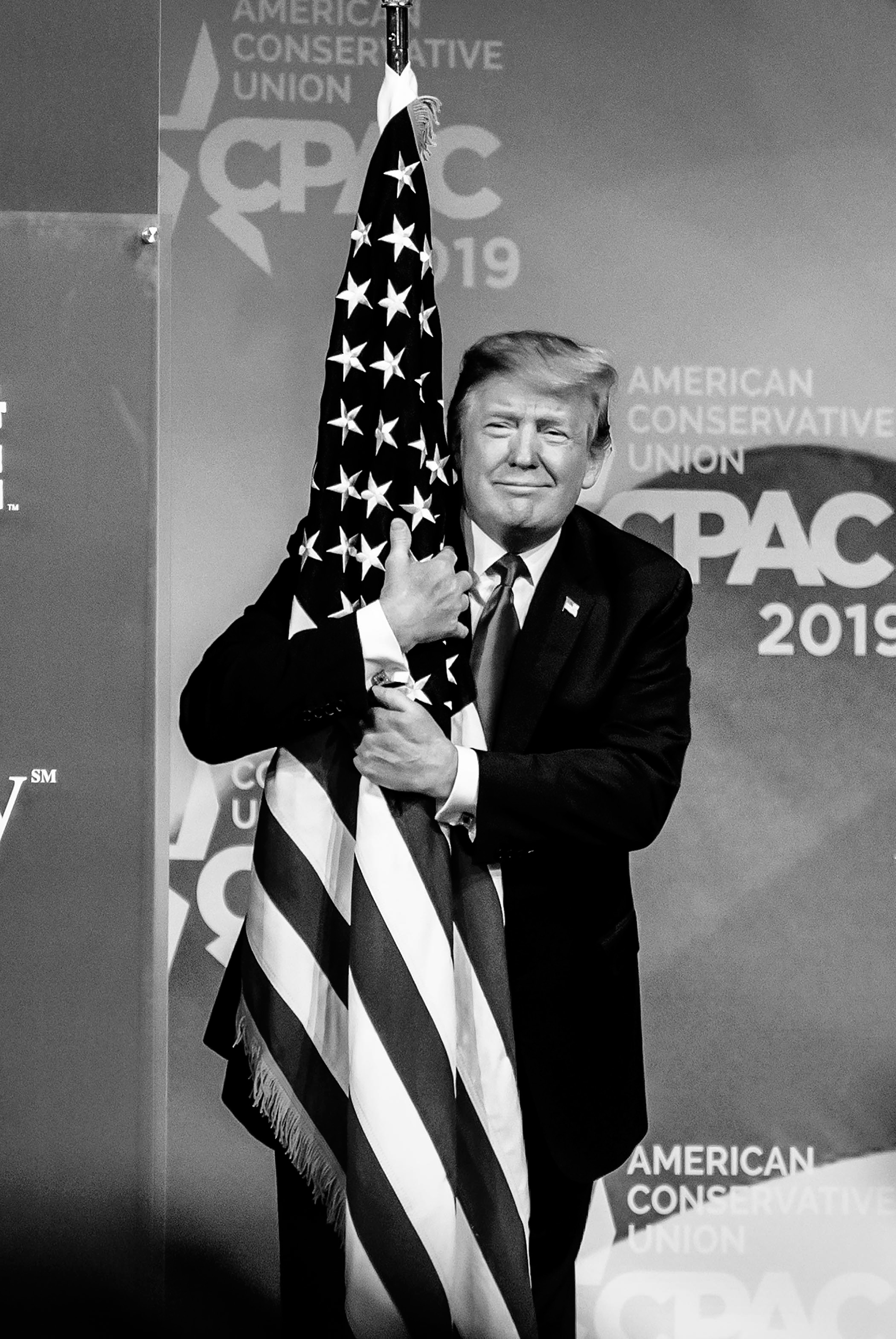 President Donald Trump hugs the American flag.
