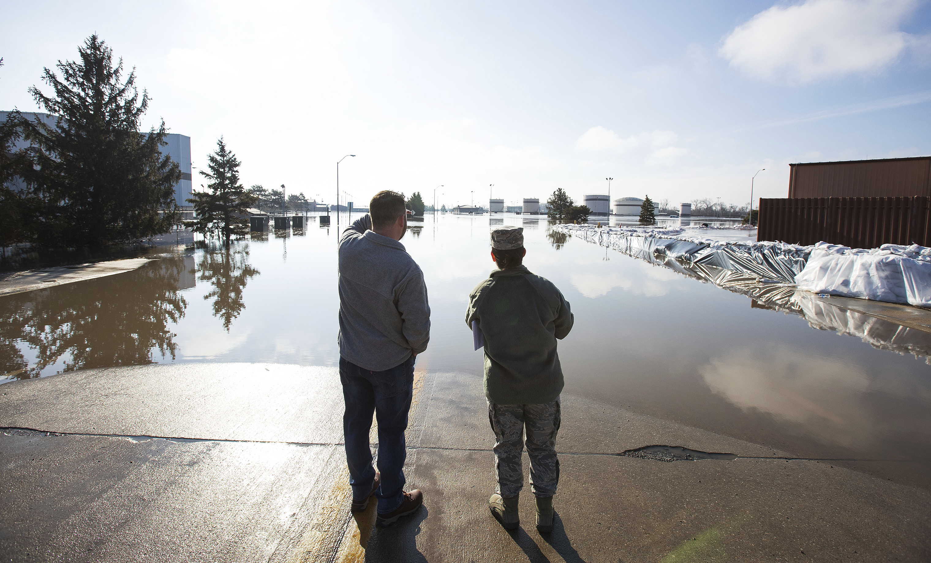 Luke Thomas and Air Force Tech Sgt. Vanessa Vidaurre look at a flooded portion of Offutt Air Force Base on March 17, 2019, in Bellevue, Nebraska.