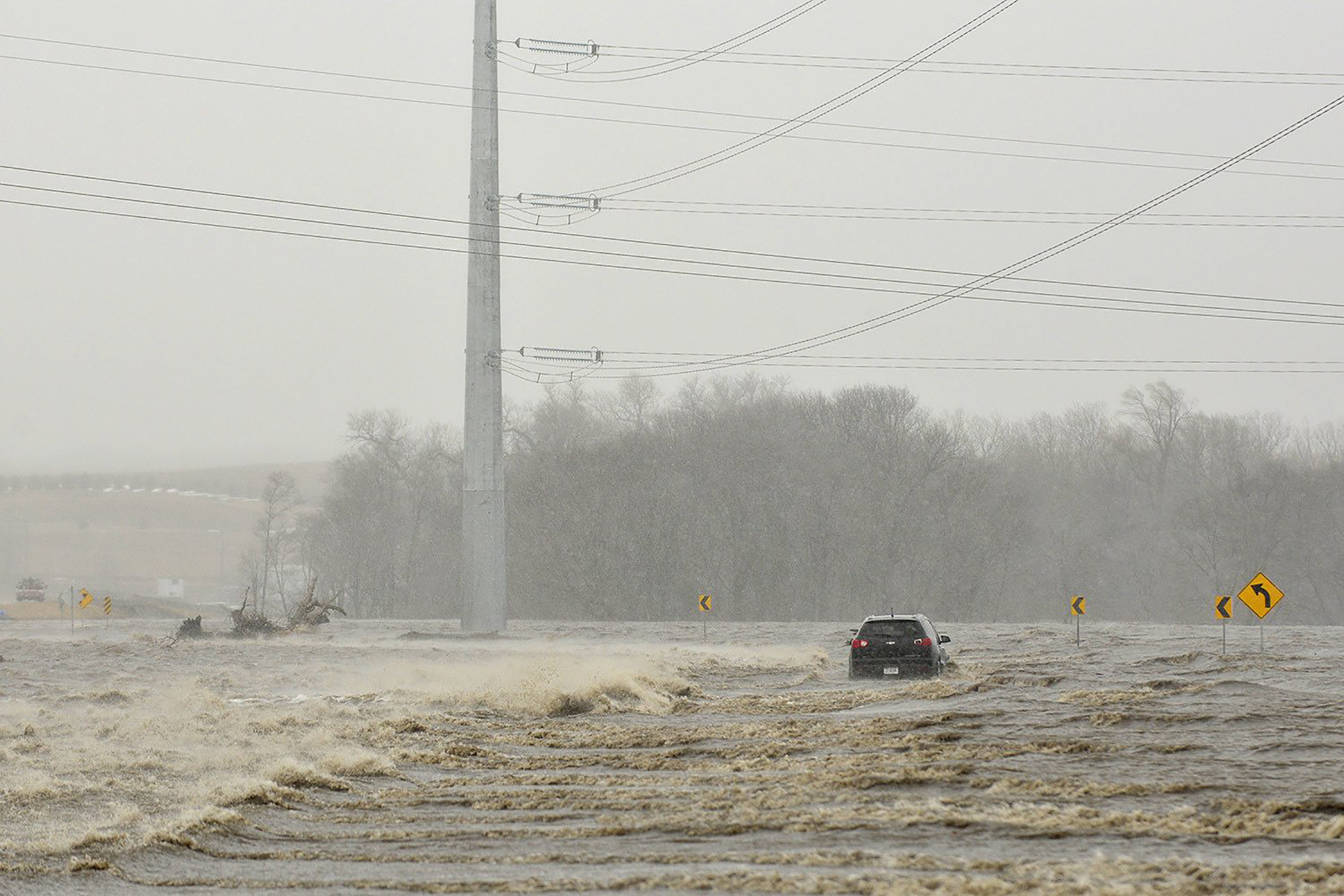An abandoned car sits on Industrial Highway in flood waters north of Norfolk, Nebraska on March 14, 2019. According to a trooper on scene, the occupant had to be rescued.