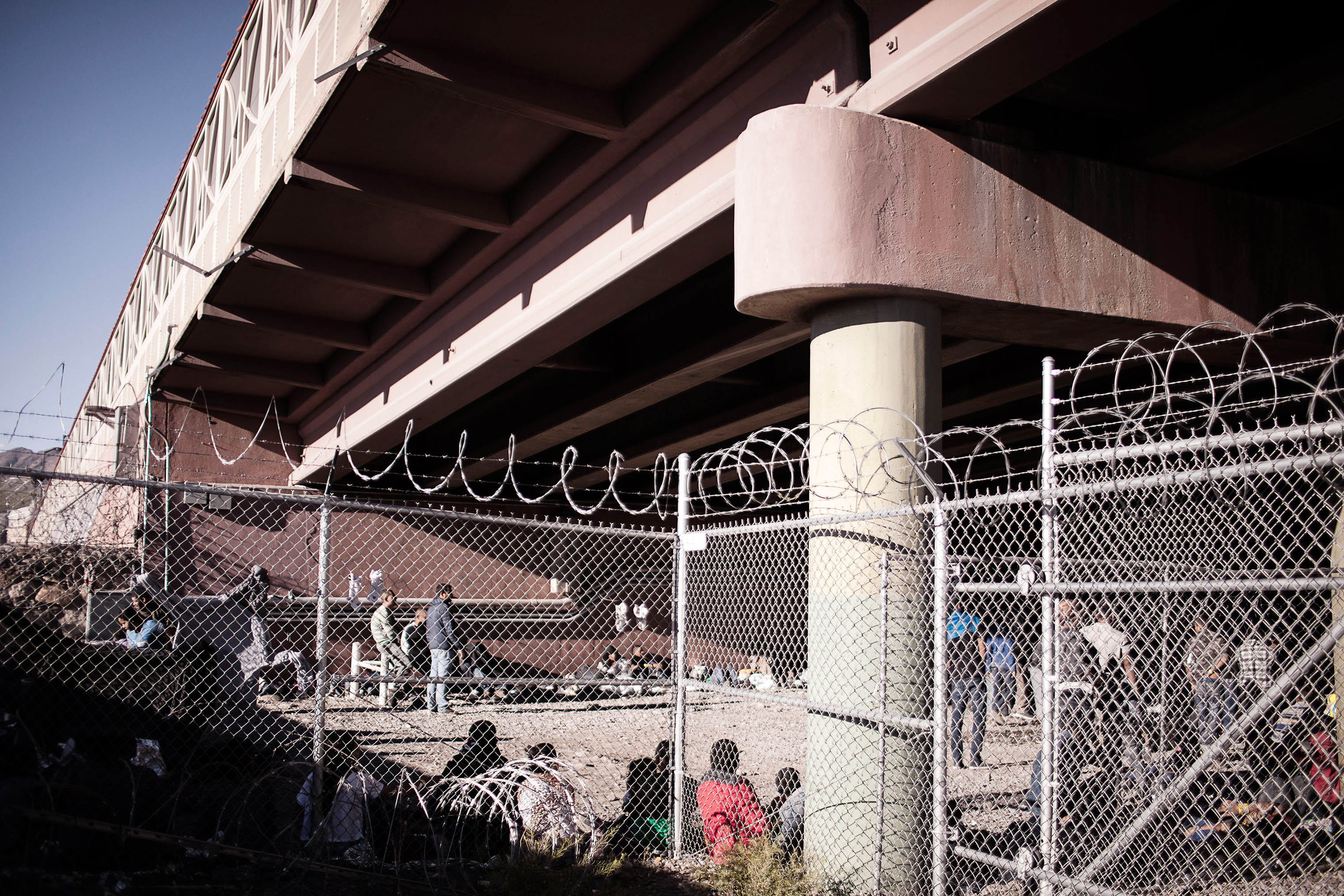 Detained migrants held within temporary fencing underneath the Paso Del Norte Bridge in El Paso, Texas on March 28, 2019. Due to the large volume of apprehensions within the area, the agency has set up a temporary facility within the last month.