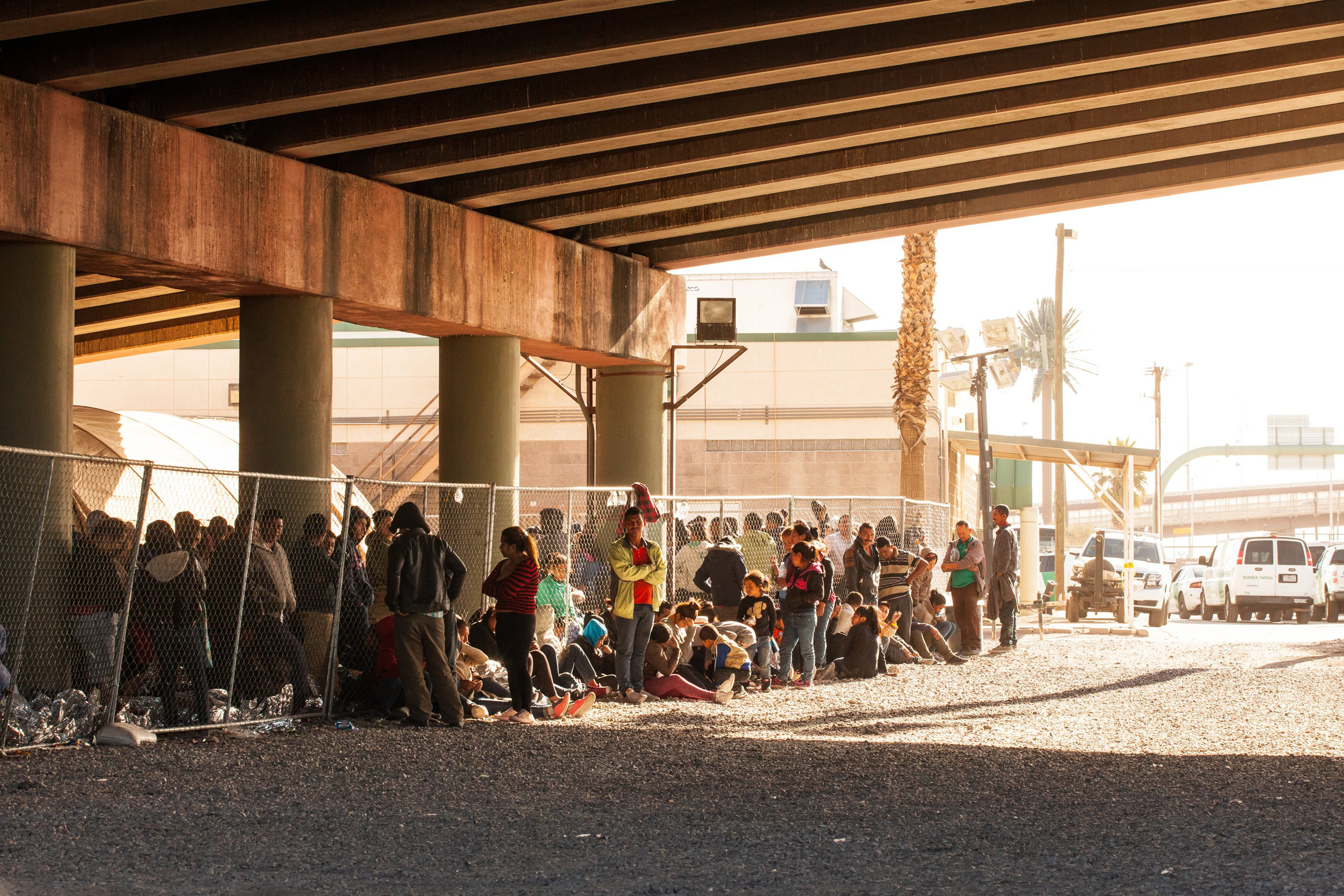 Migrants held in temporary fencing underneath the Paso Del Norte Bridge await processing on March 28, 2019 in El Paso, Texas.