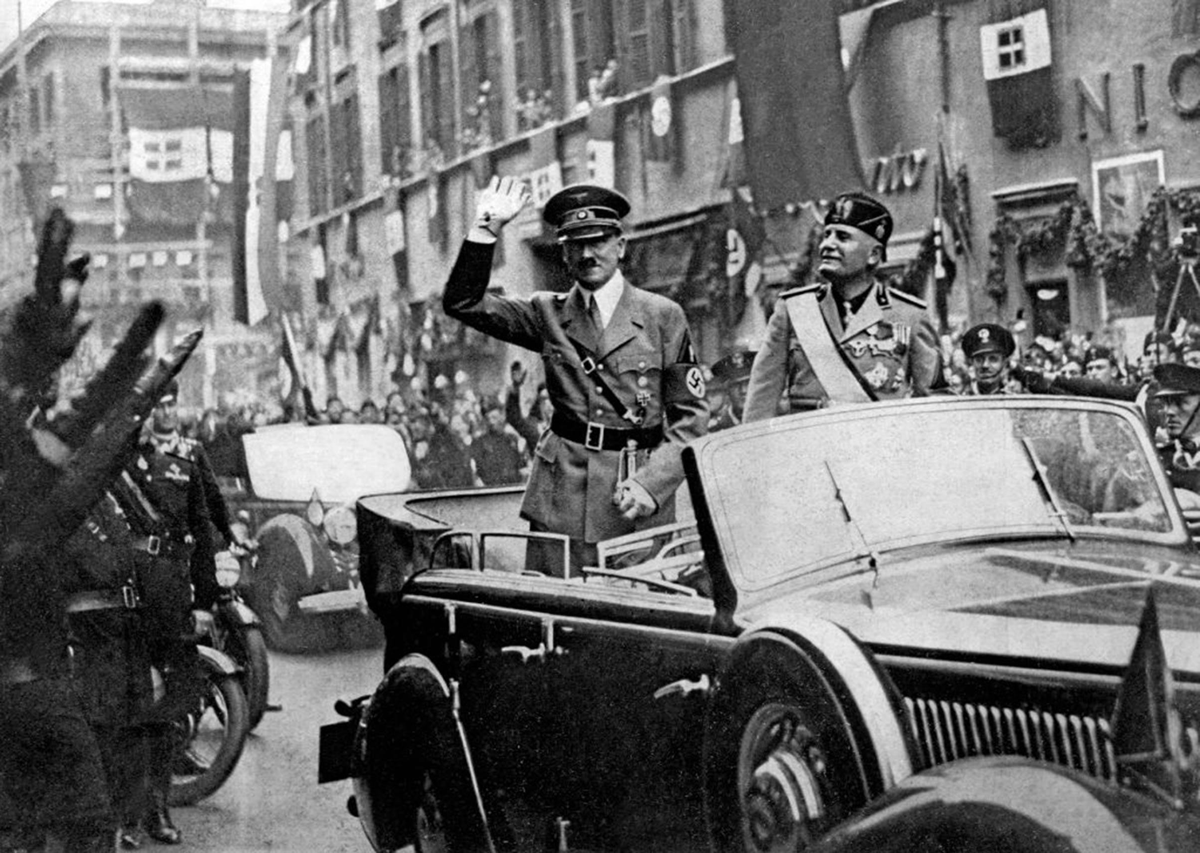 Adolf Hitler (left) and Benito Mussolini in a car, saluting the crowd that gathered along the thoroughfare Corso Vittorio Emanuele in Rome, in May 1938.