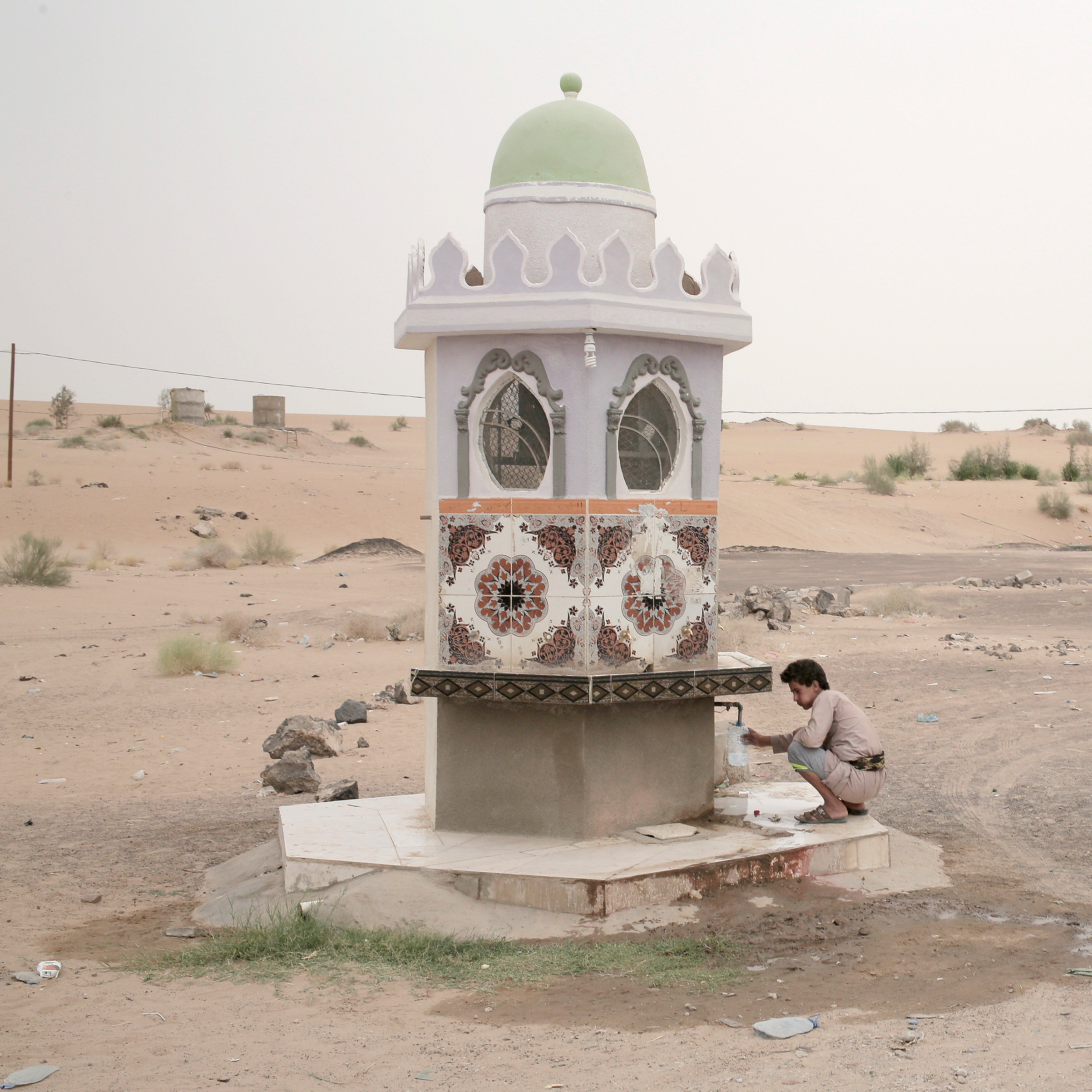A boy collects water from a roadside fountain in Marib on July 29.