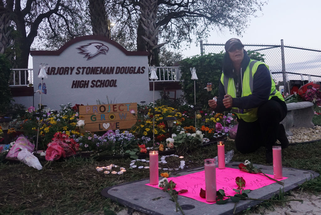 School crossing guard Wenday Behrend of Parkland lights a candle at the memorial garden outside of Marjory Stoneman Douglas High School Thursday, Feb. 14, 2019 in Parkland, Fla., on the one year anniversary of the shooting at the school.