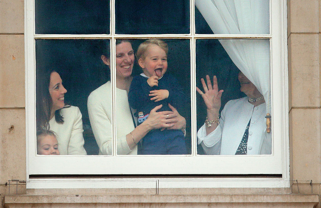 Prince George of Cambridge being held up at a window of Buckingham Palace by his nanny to watch Trooping the Colour on June 13, 2015 in London, England.