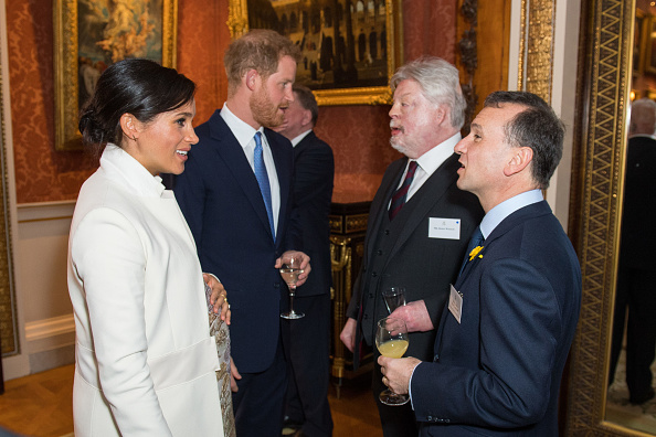 Meghan, Duchess of Sussex Duke and Prince Harry, Duke of Sussex meet Simon Weston and Alun Cairns (R) as they attend a reception to mark the fiftieth anniversary of the investiture of the Prince of Wales at Buckingham Palace in London on March 5, 2019.