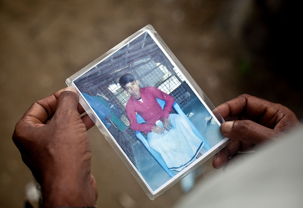 Roshid Alam holds photograph of his son, Mohammad Faisal, who was only 14 when he and 170 other Rohingya got on a boat in 2012 bound for Malaysia in this photo in Shamlapur, Bangladesh on July, 4. 2015.