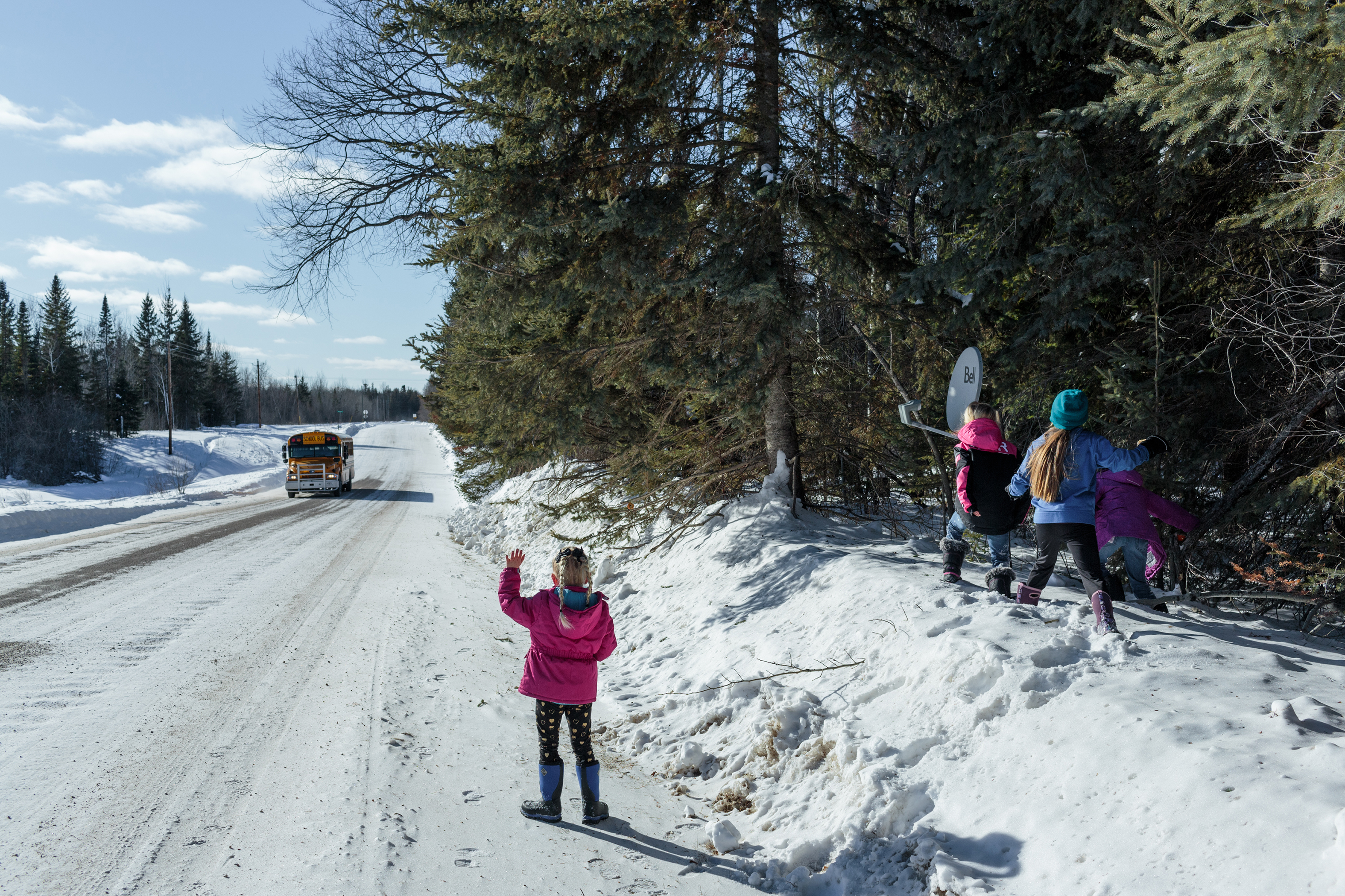 Iris Knight, 6, waves to the local schoolbus. The schoolbus transports students from the Northwest Angle to Warroad - a 2 hour commute with multiple border crossings.