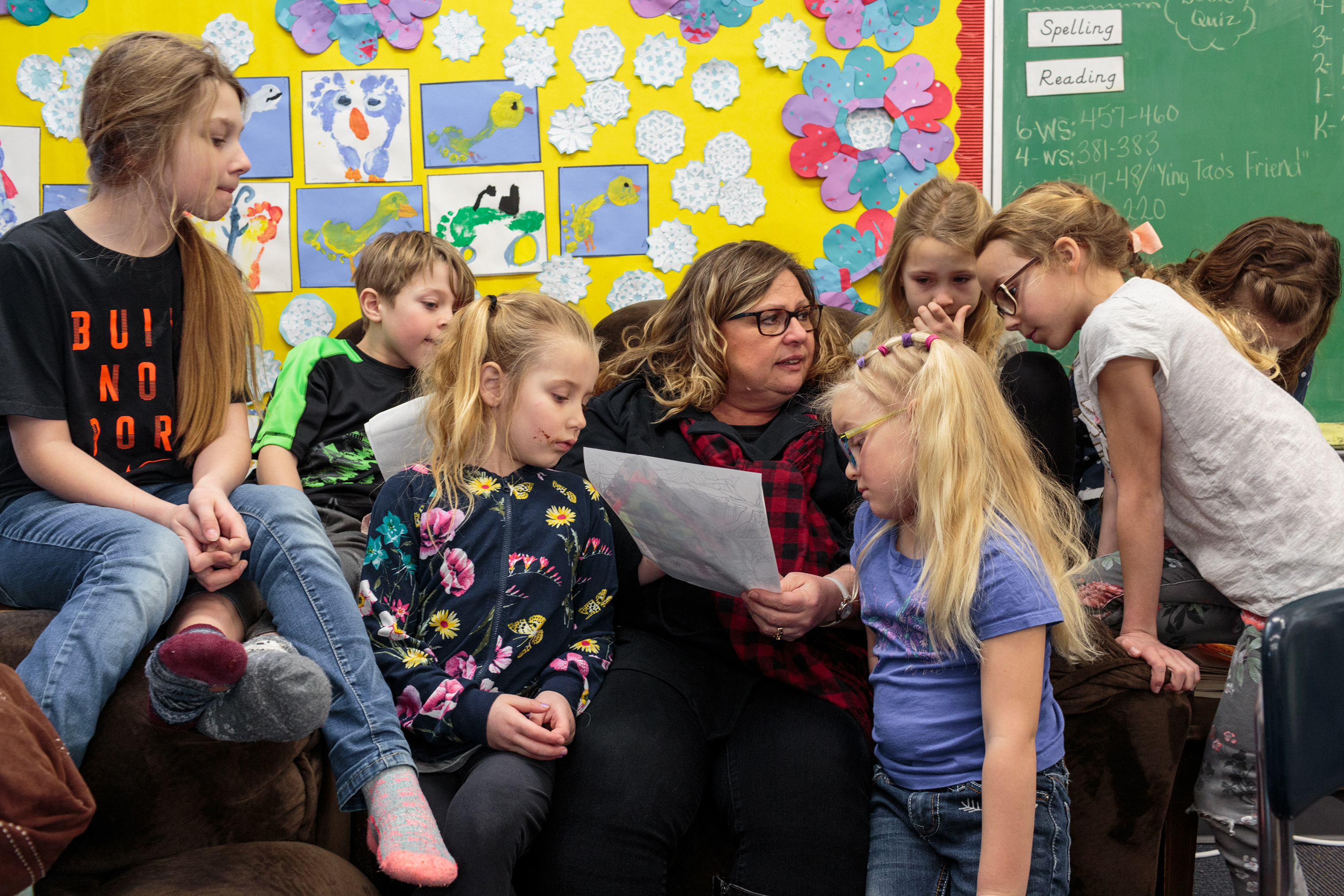 Linda Lamie, the teacher at Angle Inlet School, sits with her students while they show her their drawings and artwork.