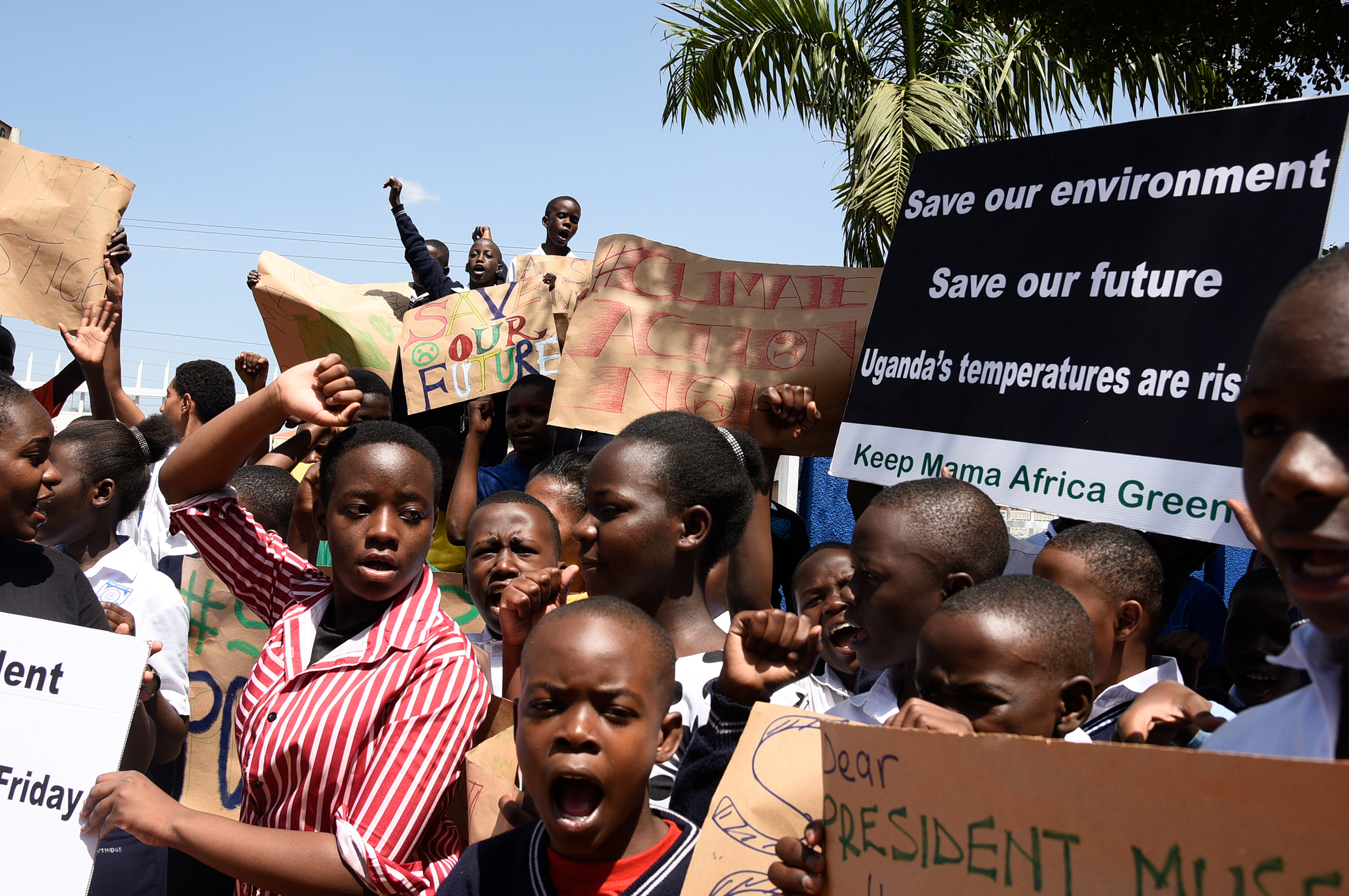 Students hold placards during a strike as part of a global day of student protests aiming to spark world leaders into action on climate change, in Kampala, Uganda on March 15, 2019.