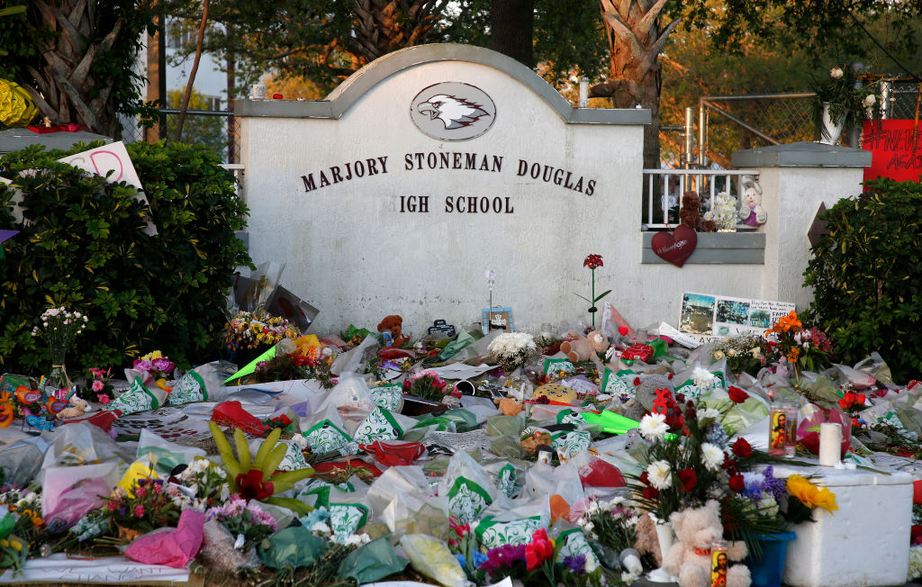 Flowers, candles and mementos sit outside one of the makeshift memorials at Marjory Stoneman Douglas High School in Parkland, Fla. after a former student died by suicide.
