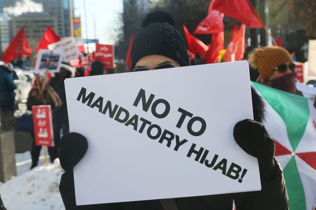 Protestor holds a sign saying 'No to Mandatory Hijab' as hundreds of Canadians take part in a protest against the Islamic Republic of Iran in Toronto, Ontario, Canada, on January 6, 2018.