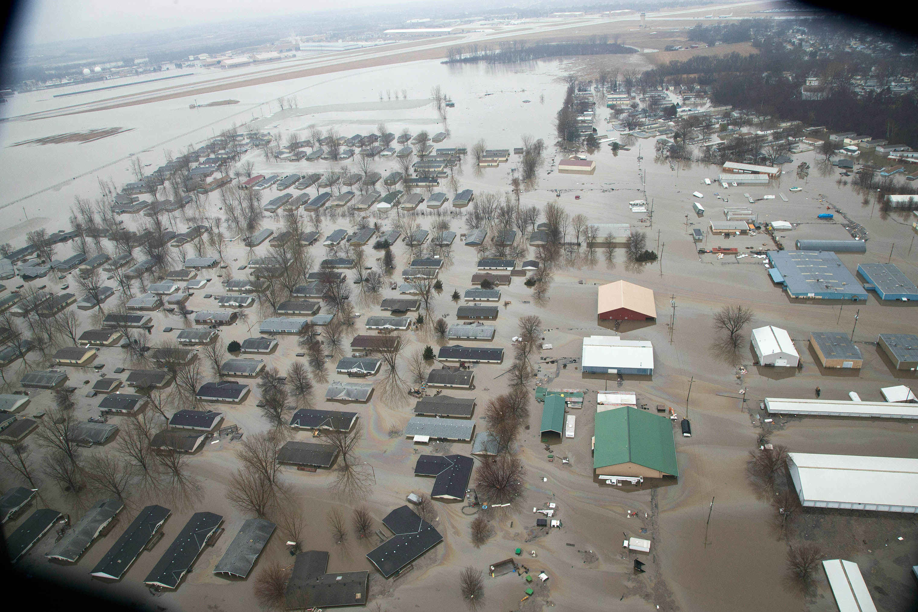 A neighborhood in Bellevue, Nebraska, is flooded by waters from the Missouri River, seen here with the Offutt Air Force Base runway.