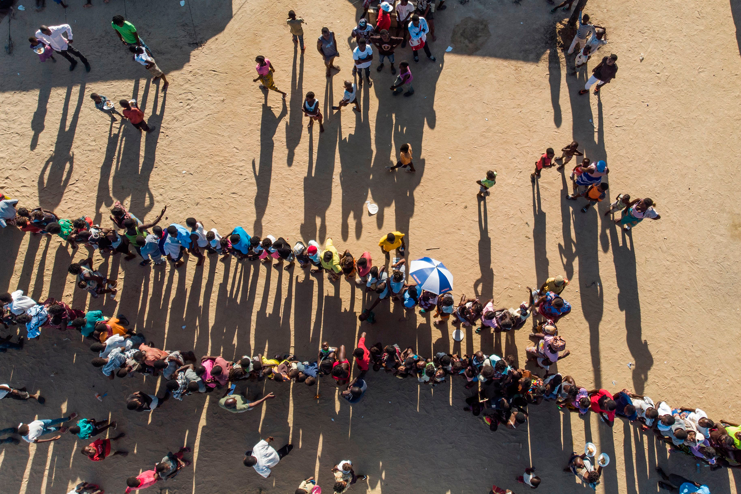 Internally displaced persons wait for supplies at the Picoco refugee camp in Beira, on April 1, 2019.