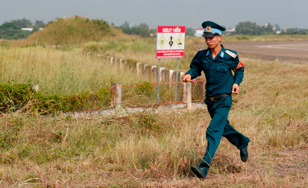 A Vietnamese soldier runs past the dioxin contaminated area of the Bien Hoa airbase on the outskirts of Ho Chi Minh City, Vietnam, on Oct.17, 2018.