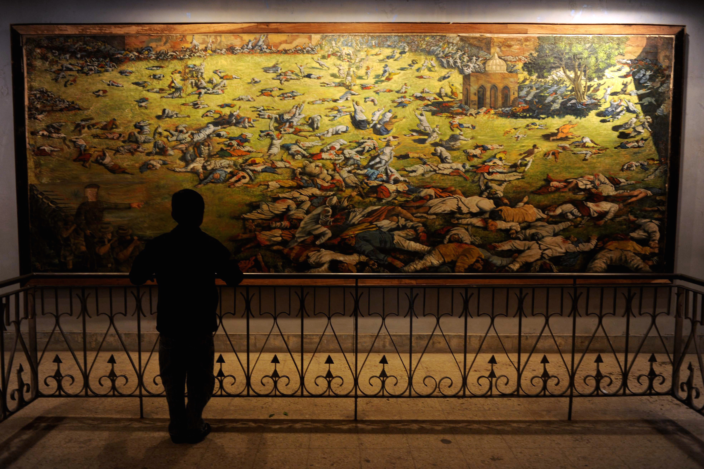 A young visitor looks at a painting depicting the Amritsar Massare at Jallianwala Bagh in Amritsar on Feb. 4, 2010.