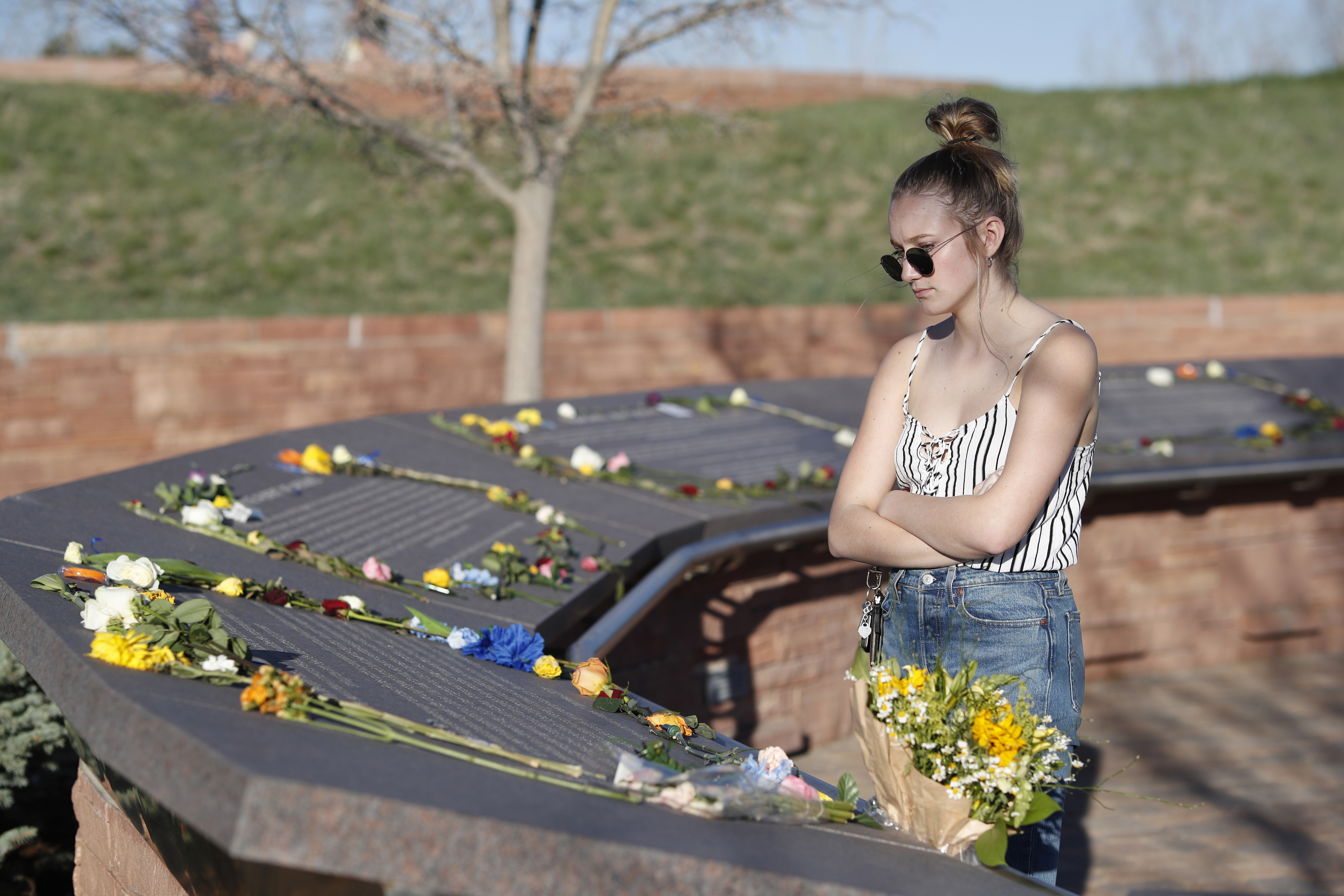 Sixteen-year-old Maren Strother of Denver looks over the plaques on April 19, 2019 for victims of the Columbine High School massacre before a vigil marking the 20th anniversary of the shooting in Littleton, Colo.
