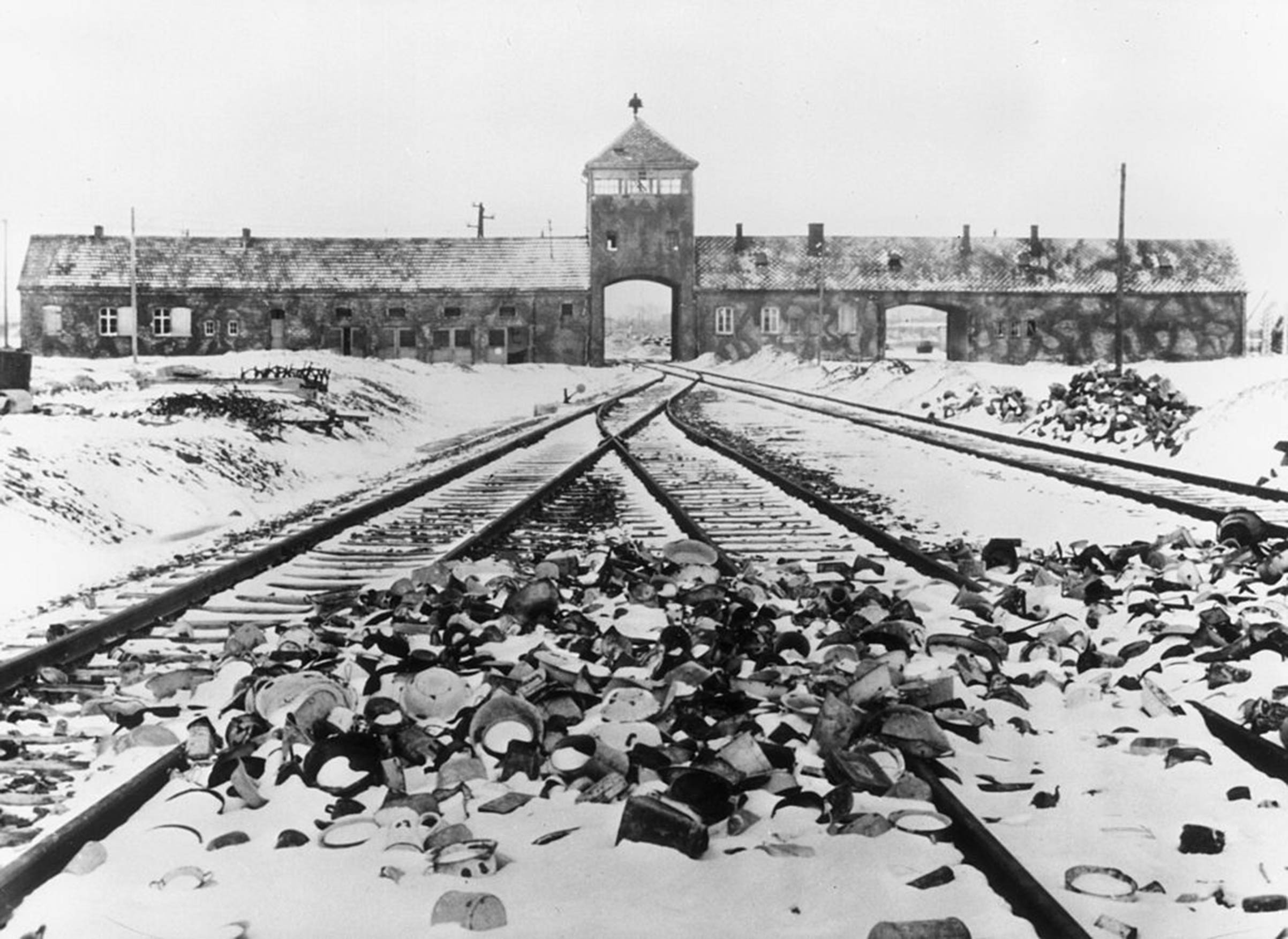 Snow-covered personal effects of those deported to the Auschwitz concentration camp in Poland litter the train tracks leading to the camp's entrance, circa 1945.