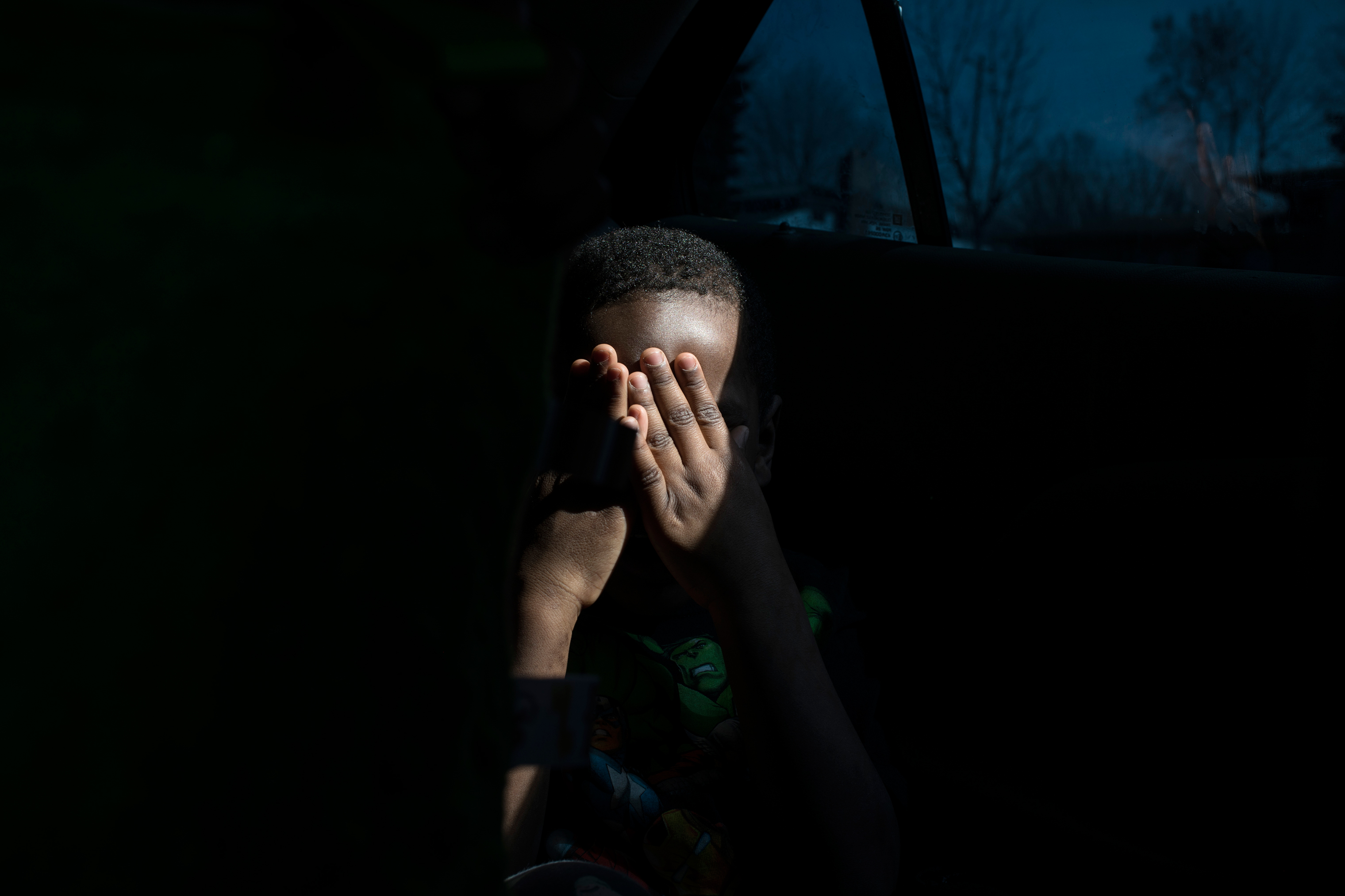 Sincere hides his face after getting picked up from school in April 2018.