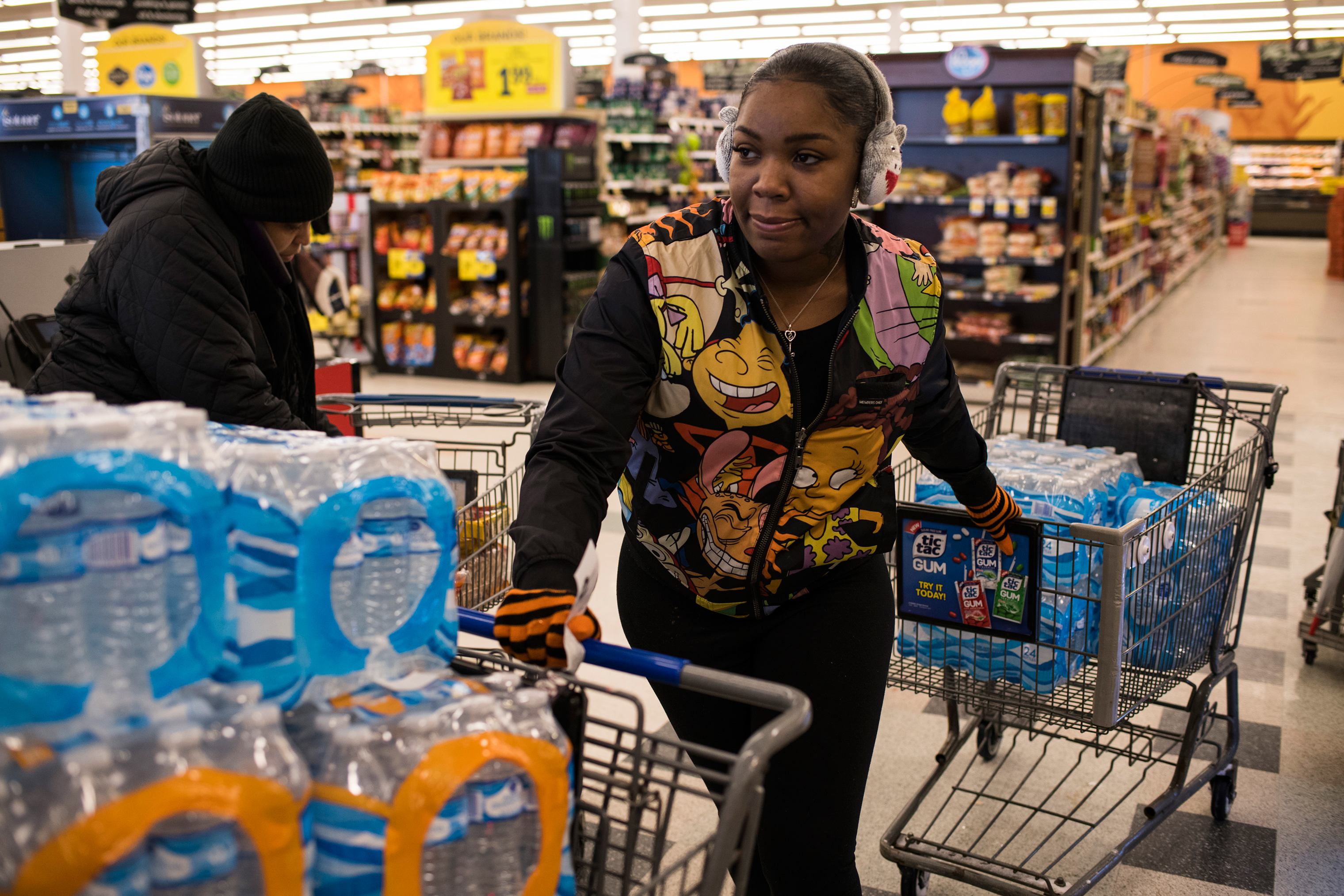 Flint residents ask Hawk for help getting safe water; she's seen here in January buying cases to distribute.