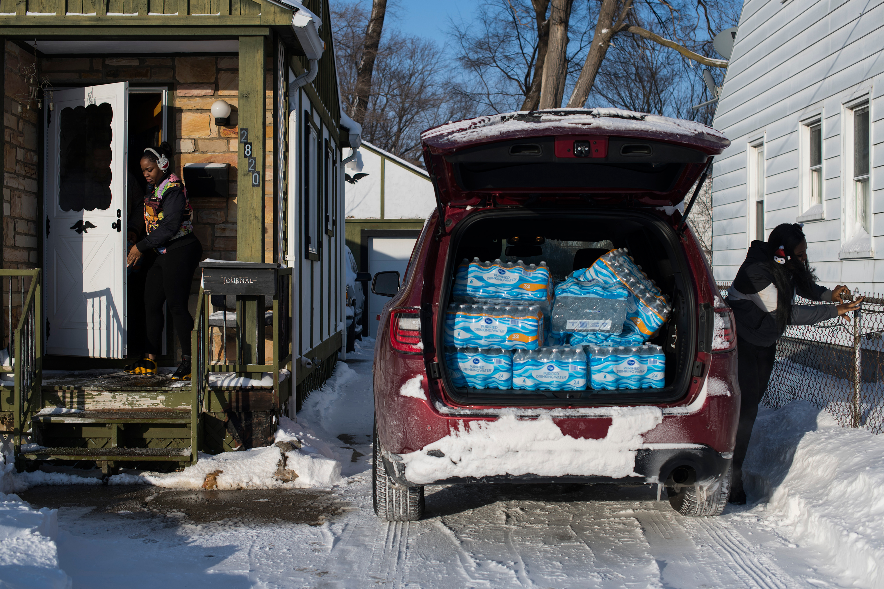 Hawk and a friend deliver cases of water, which she bought, to Flint residents in January.