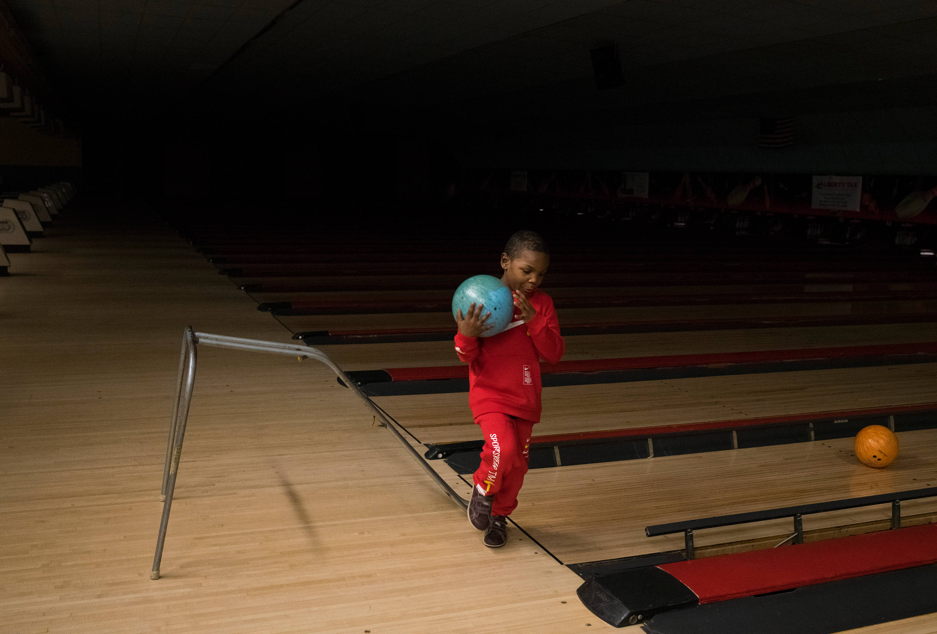 Sincere picks up his ball while bowling for his sixth birthday party in Grand Blanc, Mich., on Feb. 4.