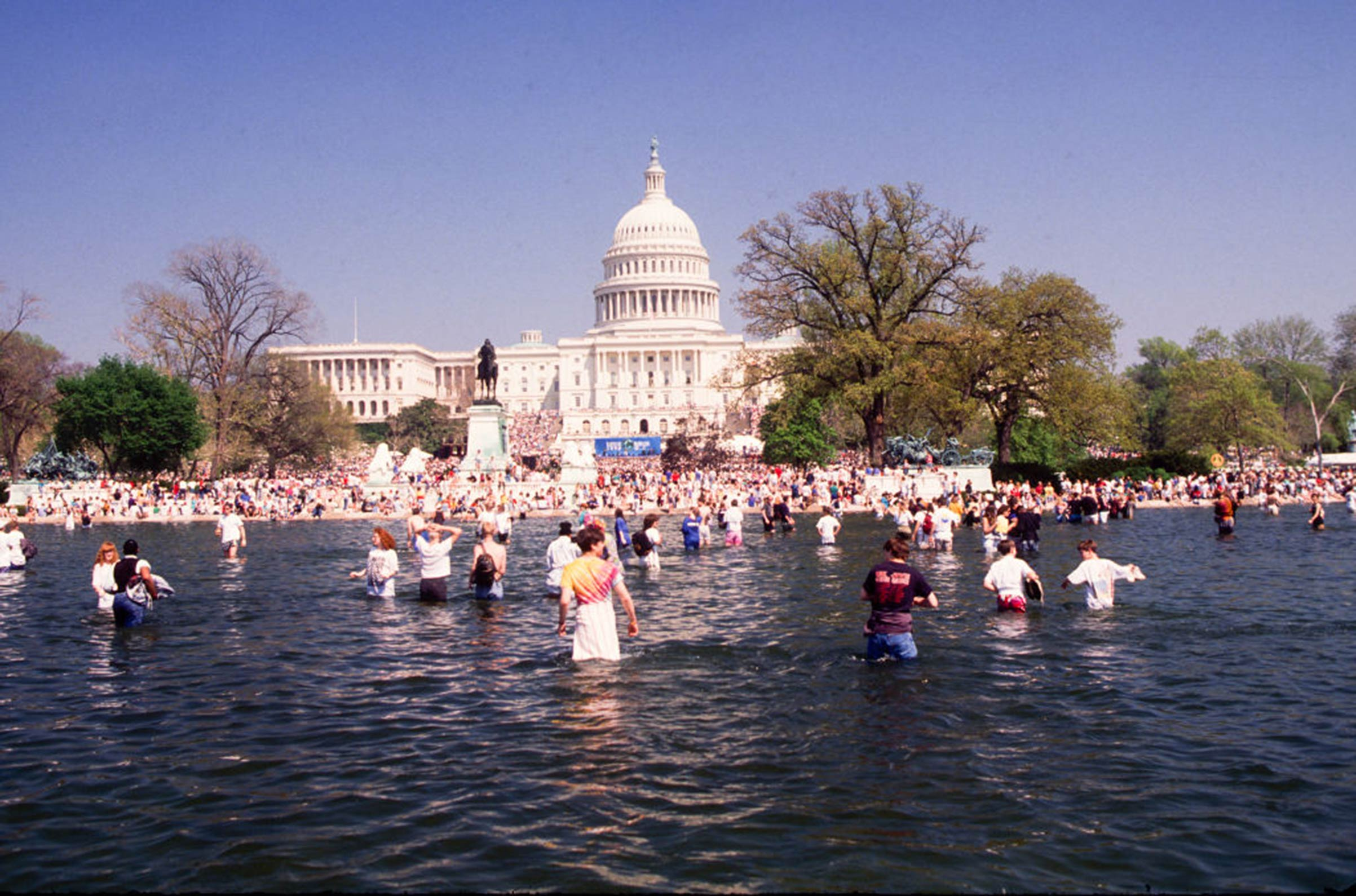 View of the crowd gathering for an Earth Day rally on the U.S. Capitol grounds, some in the Capitol Reflecting Pool on April 22, 1990, in Washington D.C.