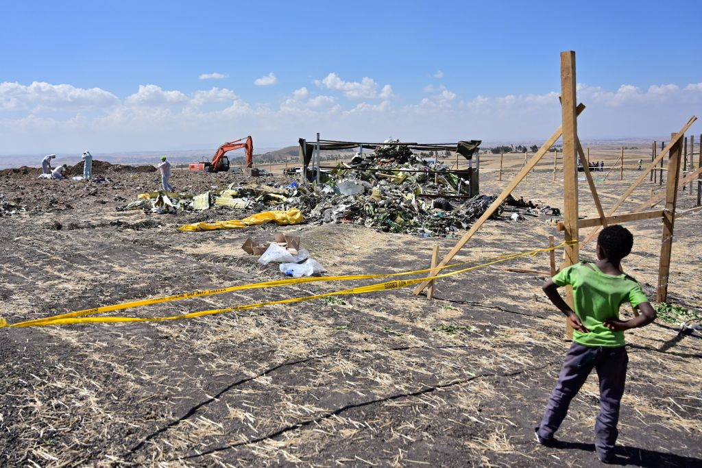A boy looks as forensic investigators comb the ground for DNA evidence near a pile of twisted airplane debris at the crash site of an Ethiopian airways flight operated Boeing 737 MAX aircraft on March 16, 2019 at Hama Quntushele village near Bishoftu in Oromia region. Pilots on the Ethiopian Airlines flight that crashed last month followed Boeing protocol as they tried to save the Boeing Co. 737 Max jet, a source said.