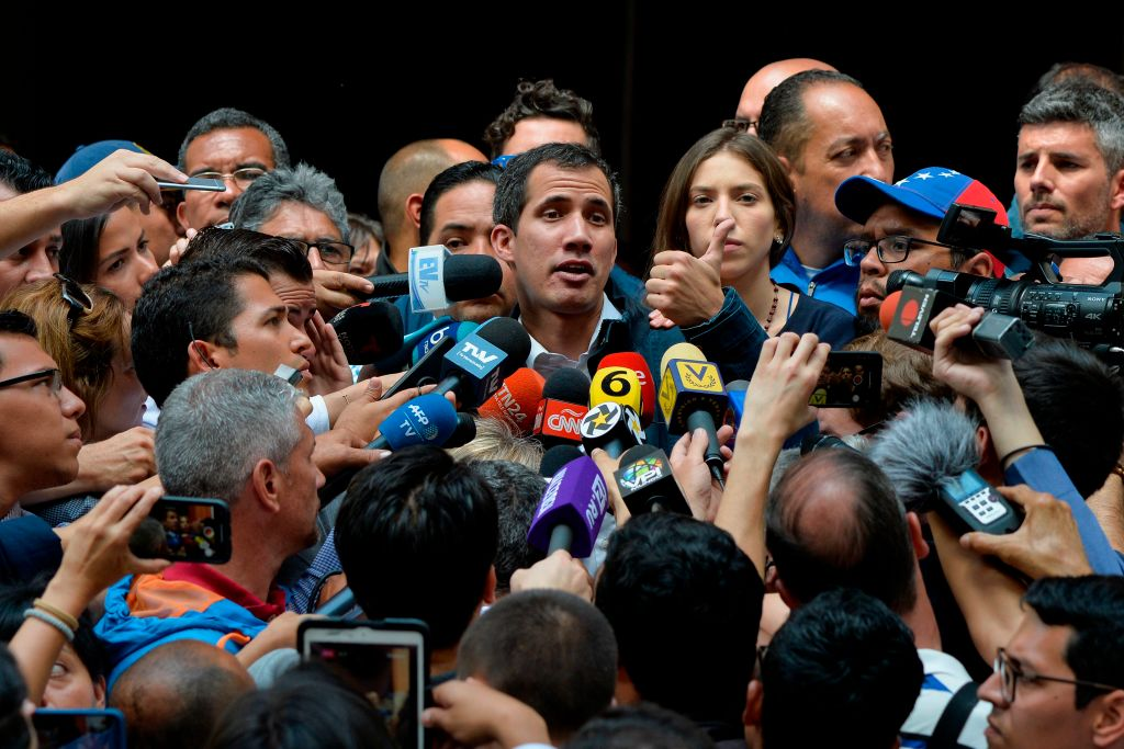 Venezuela's National Assembly head and self-proclaimed  acting president  Juan Guaido (C) speaks to the press after attending a mass in honour to the fallen in the fight for freedom, political prisoners and the exiled, at the San Jose church in Caracas on January 27, 2019.