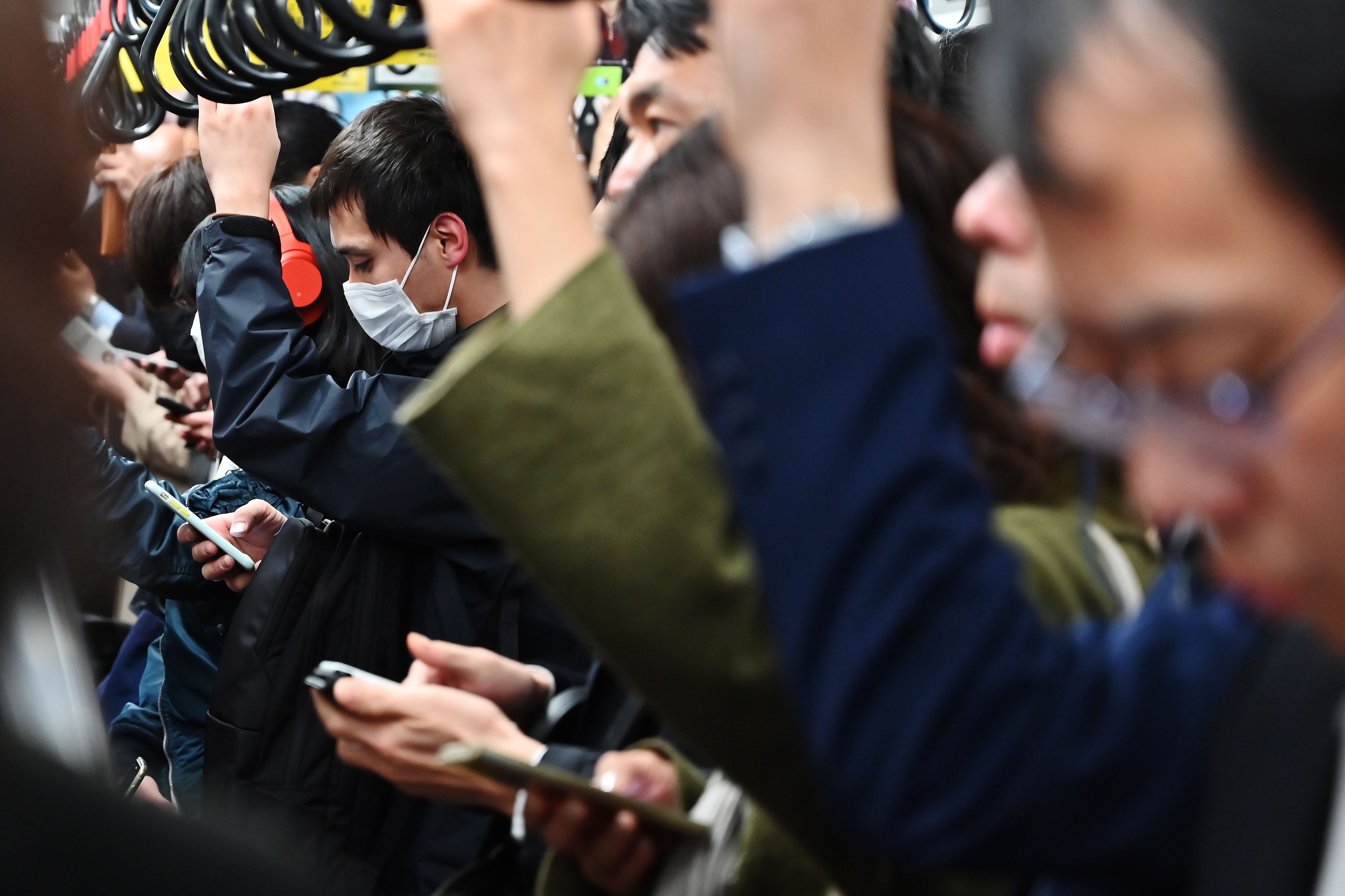 Commuters use their mobile phones while travelling on a coach of the Tokyo Metro network in Tokyo on March 26, 2019.