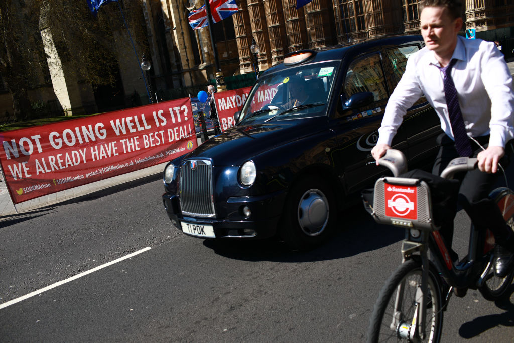 Traffic passes anti-Brexit banners outside the Houses of Parliament in London, England, on April 10, 2019